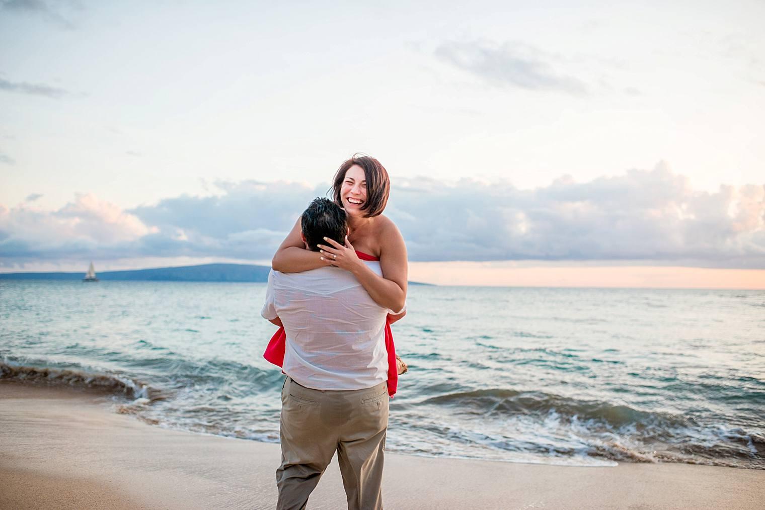 man picking up fiance on beach