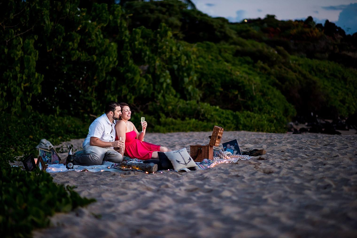 engaged couple enjoying champagne on the beach