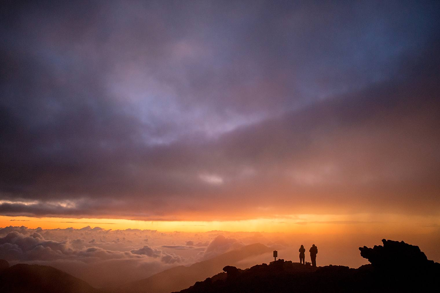 silhouette of a couple on a mountain at sunrise