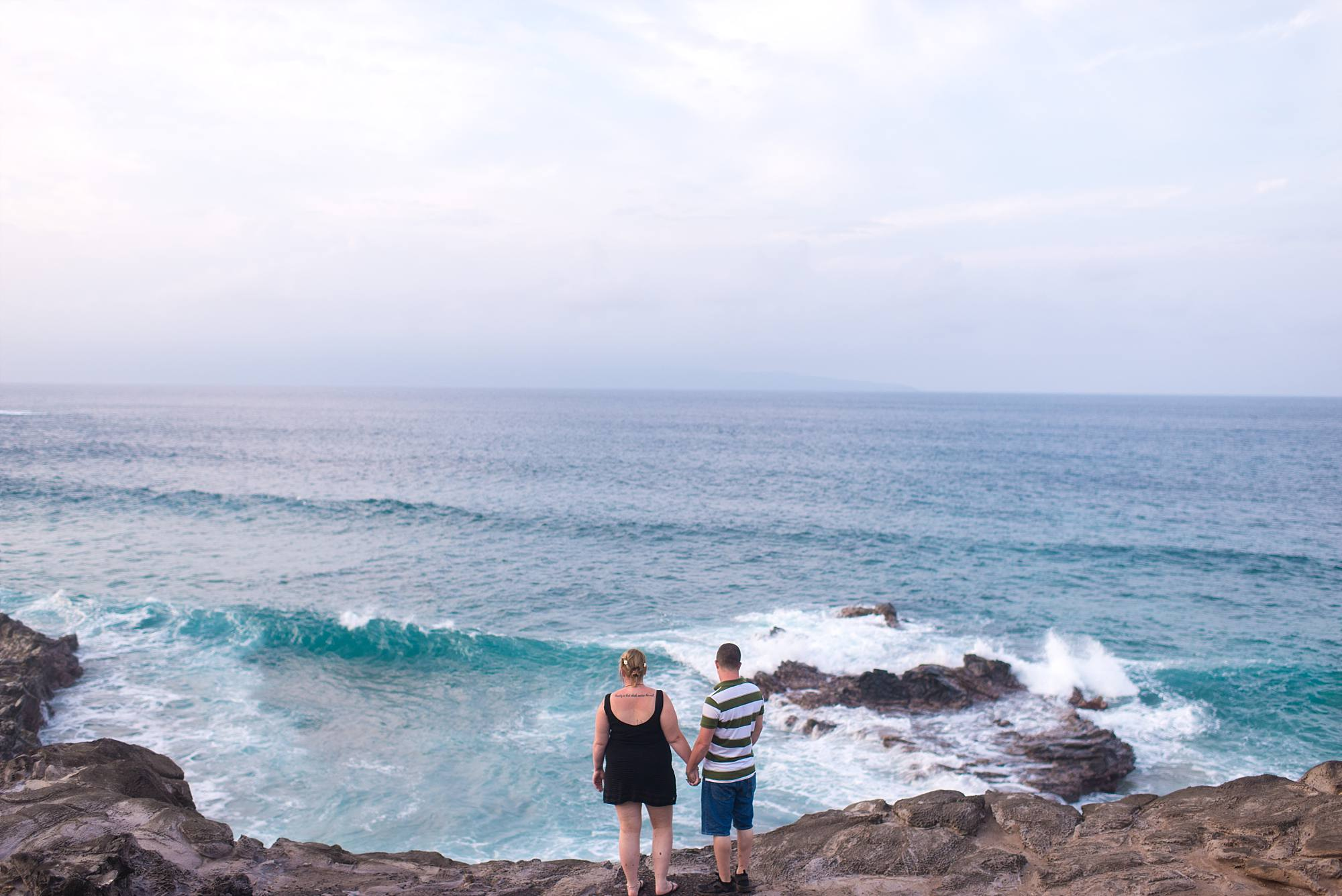 couple looking out over the crashing waves of Maui