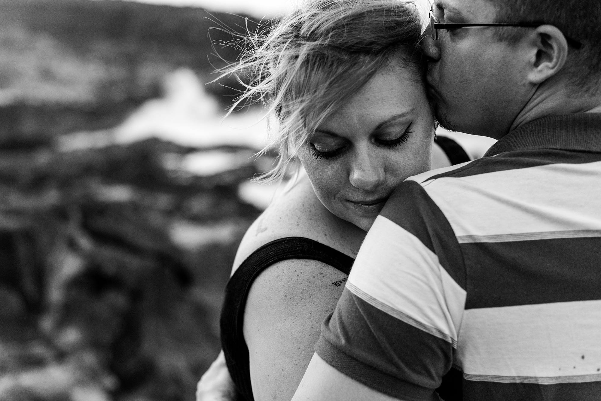 close up of man and woman hugging he's kissing her head