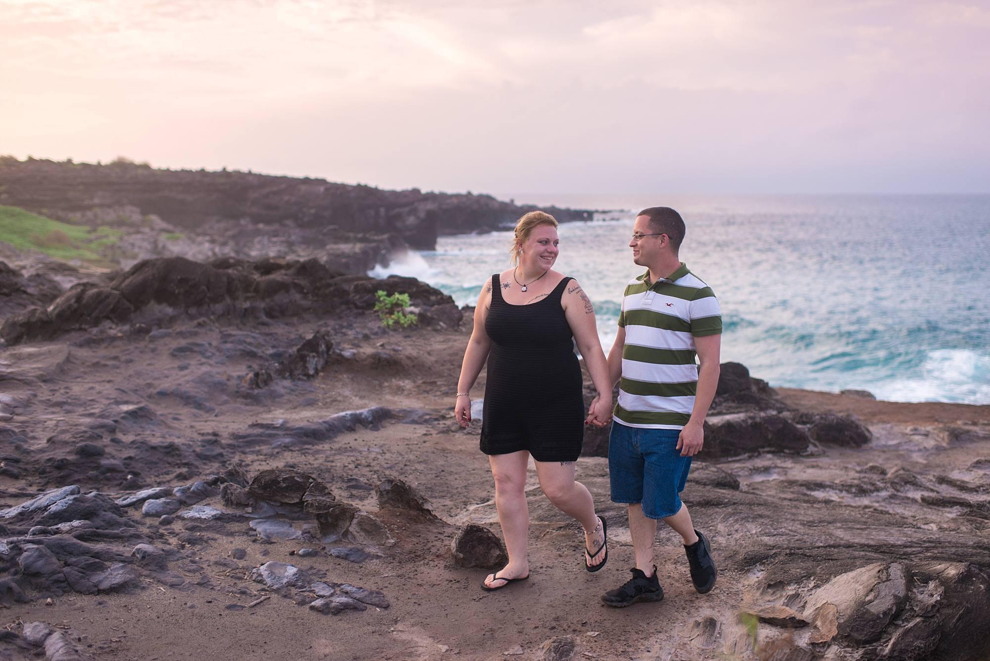 couple walking on rocks near ocean