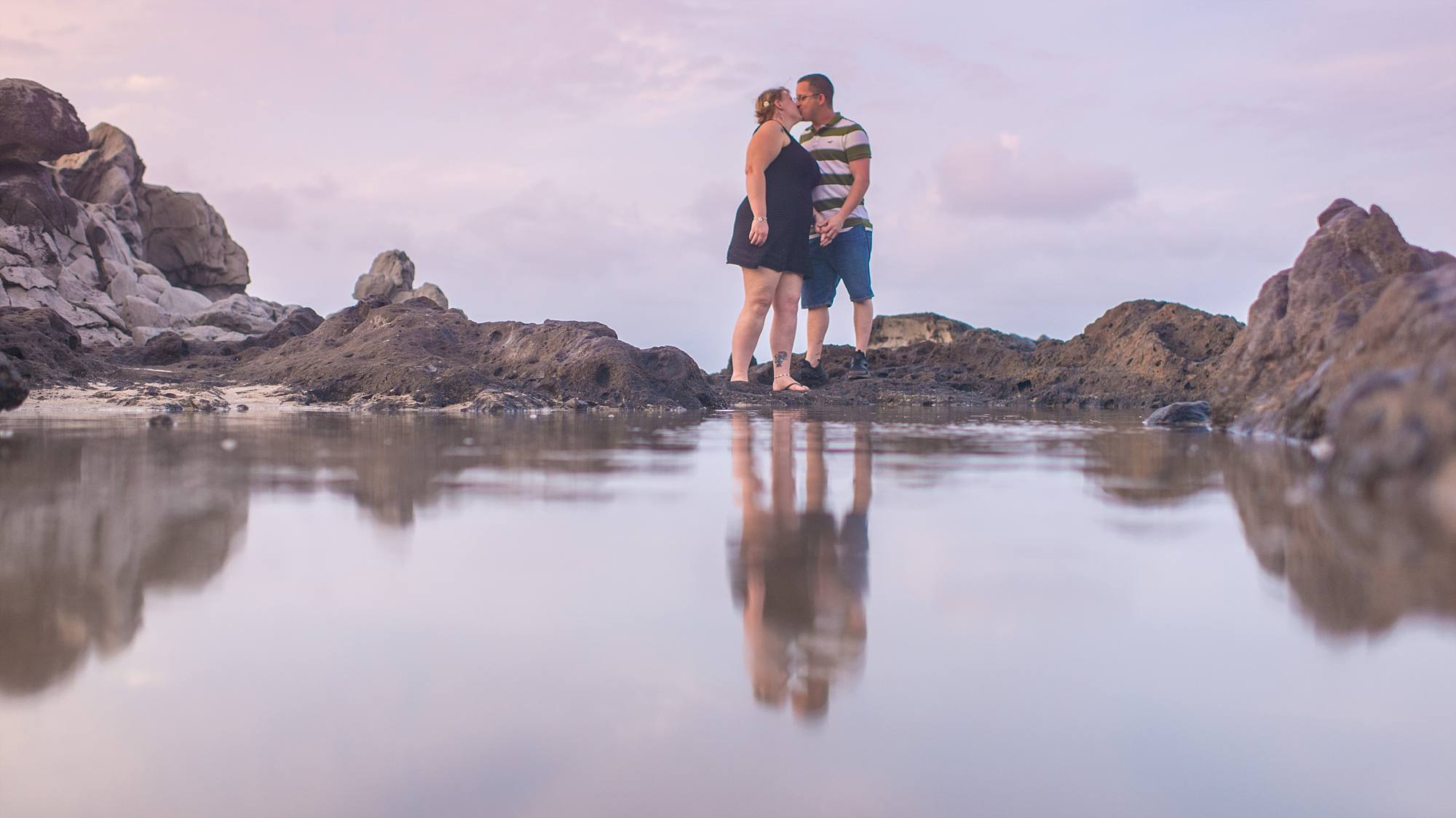fiances kissing and reflection in a tidepool