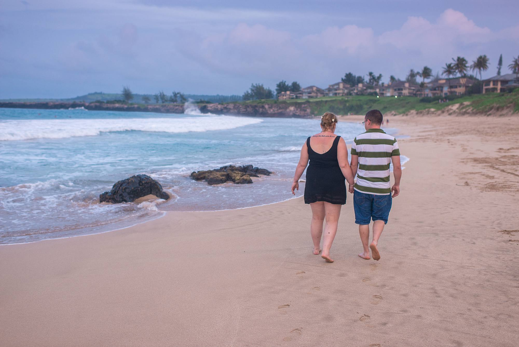 newly engaged couple walking hand in hand down the beach