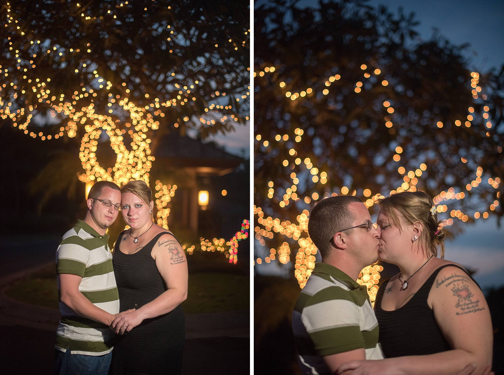 couple kissing in front of Maui christmas lights