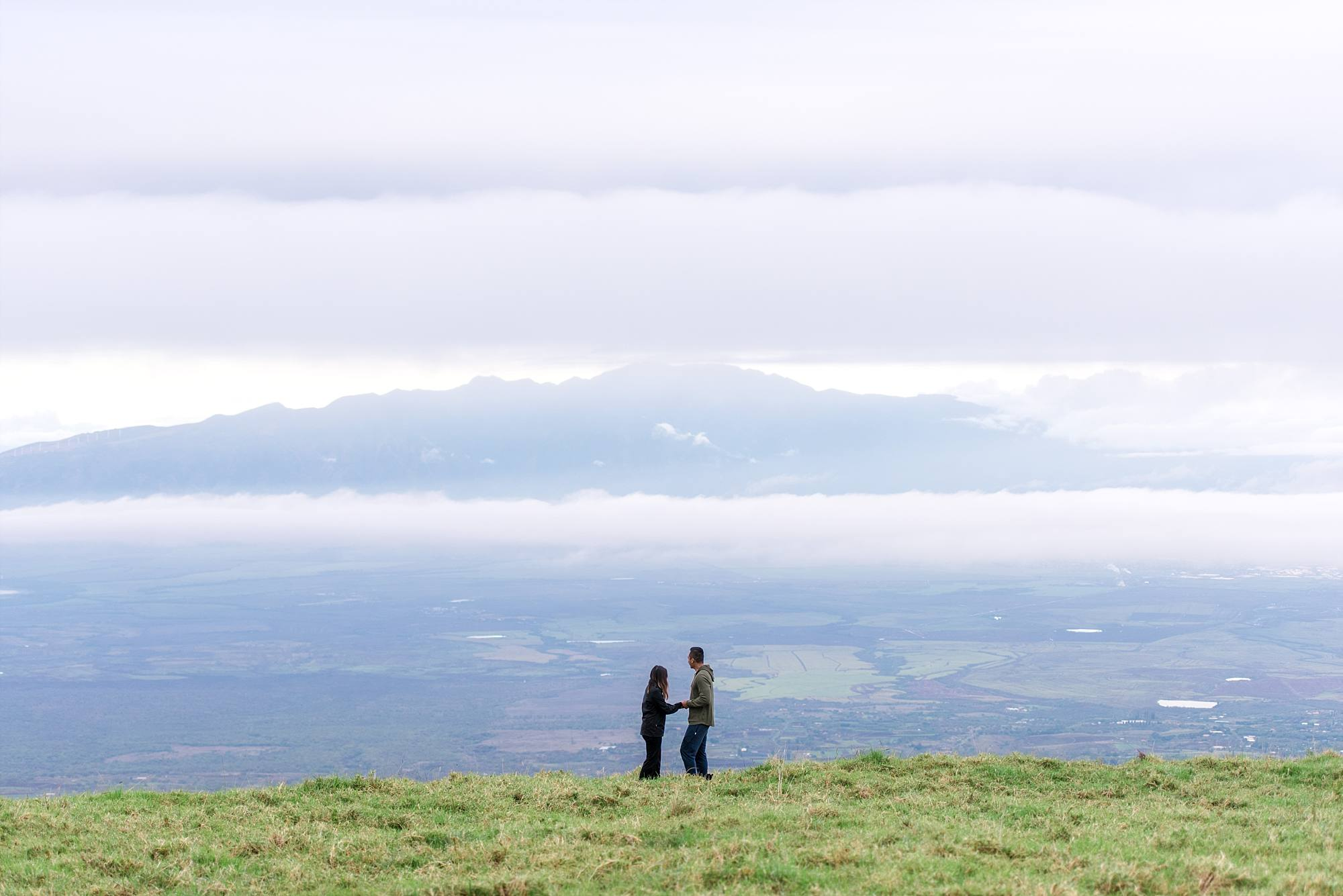 couple standing on cliffside of Haleakala about to propose