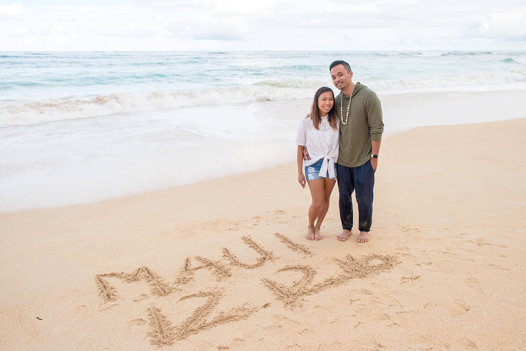 couple standing on sand with engagement date etched into sand