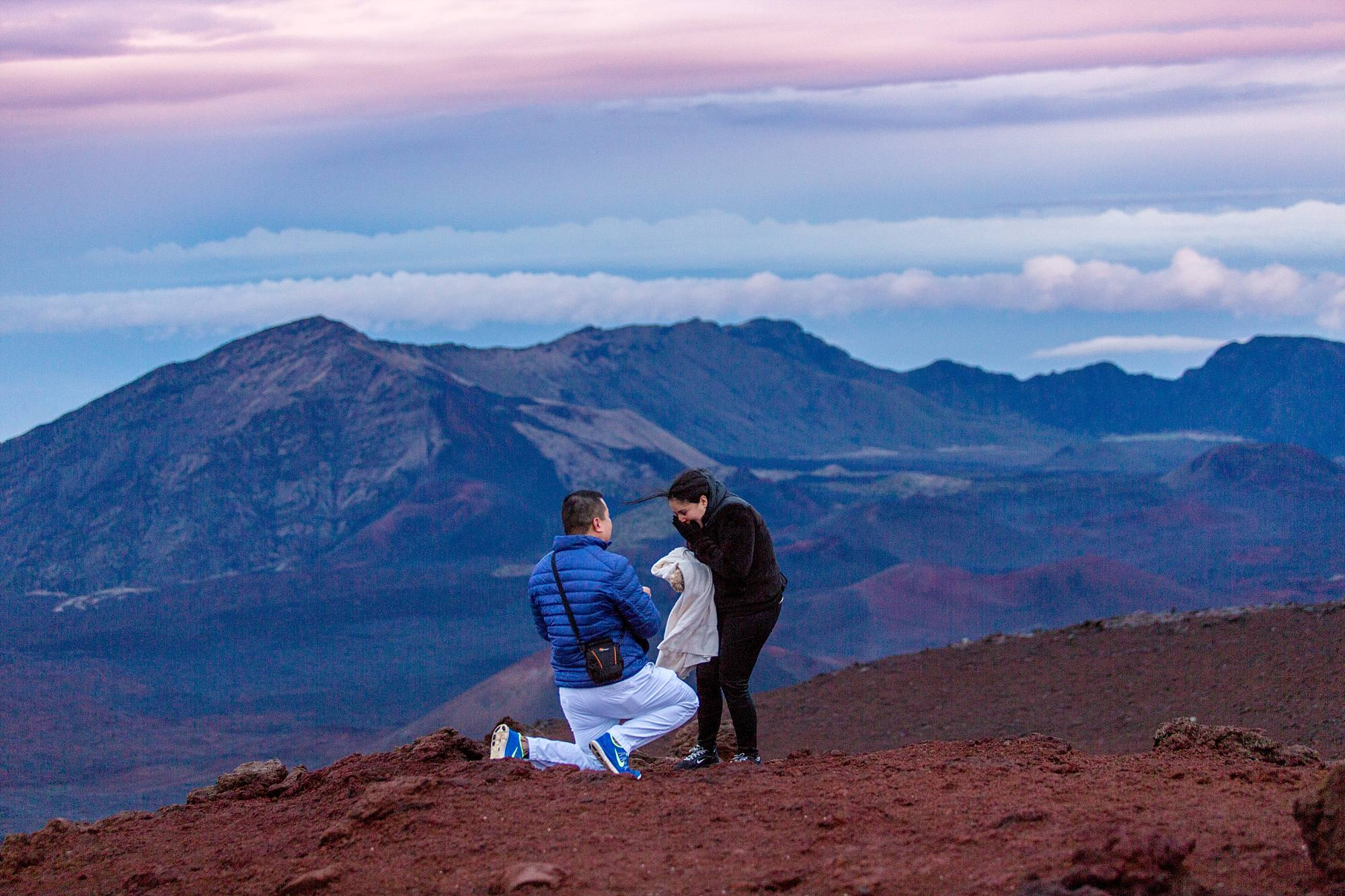 woman surprised to be getting engaged mountains in background