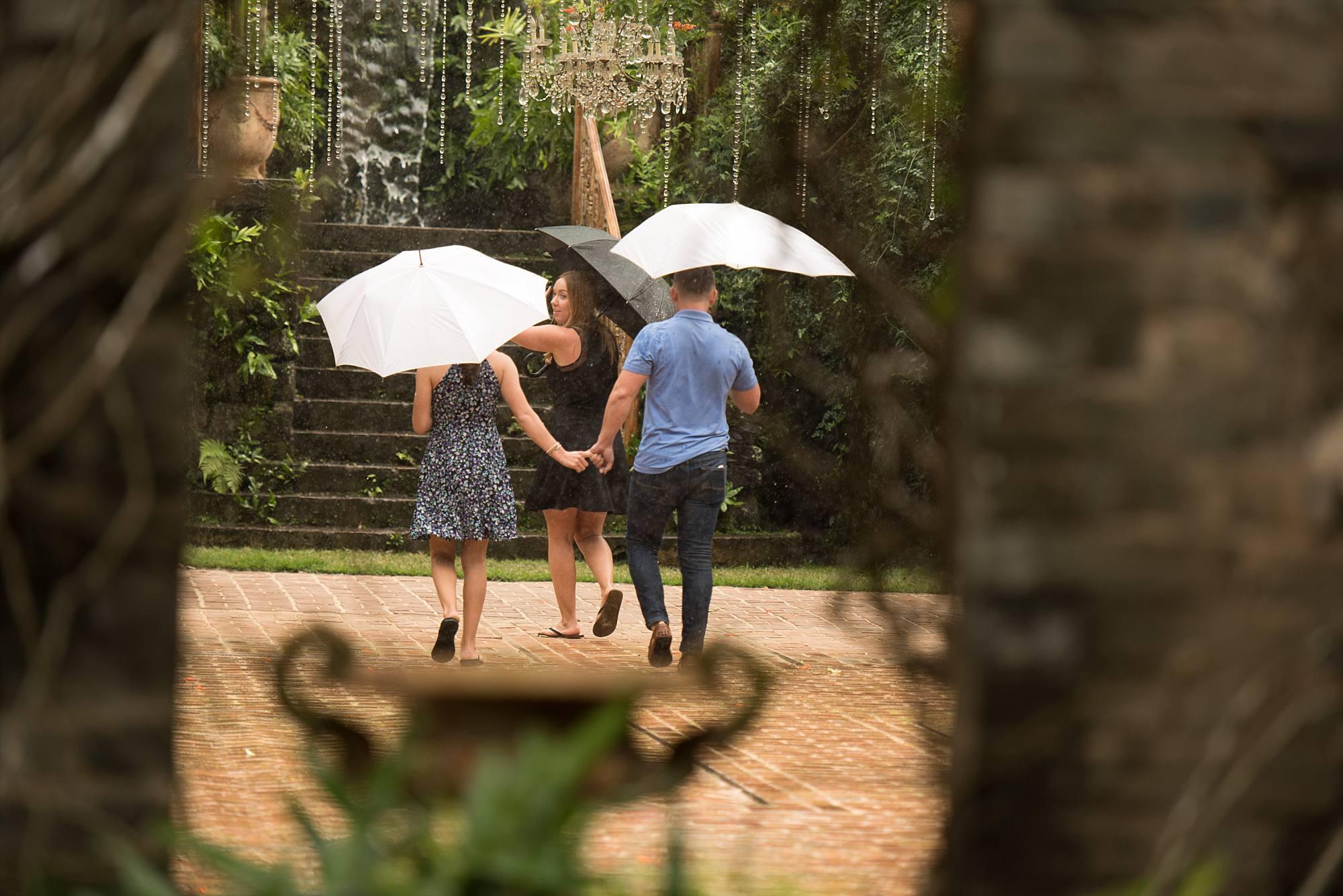couple walking away both holding umbrellas