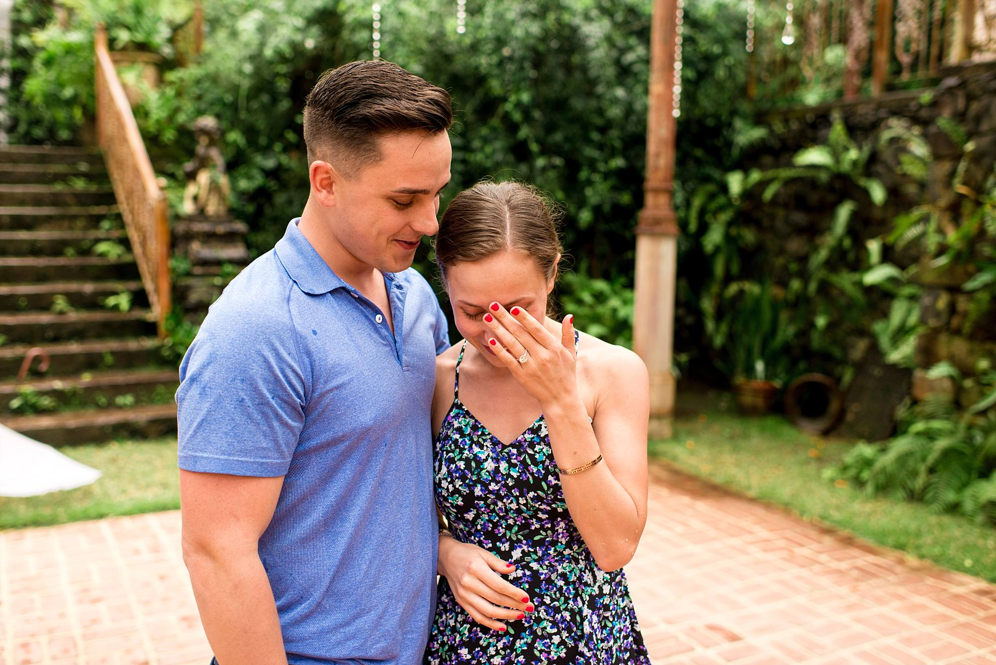 woman touching forehead man holding her, excited to be engaged