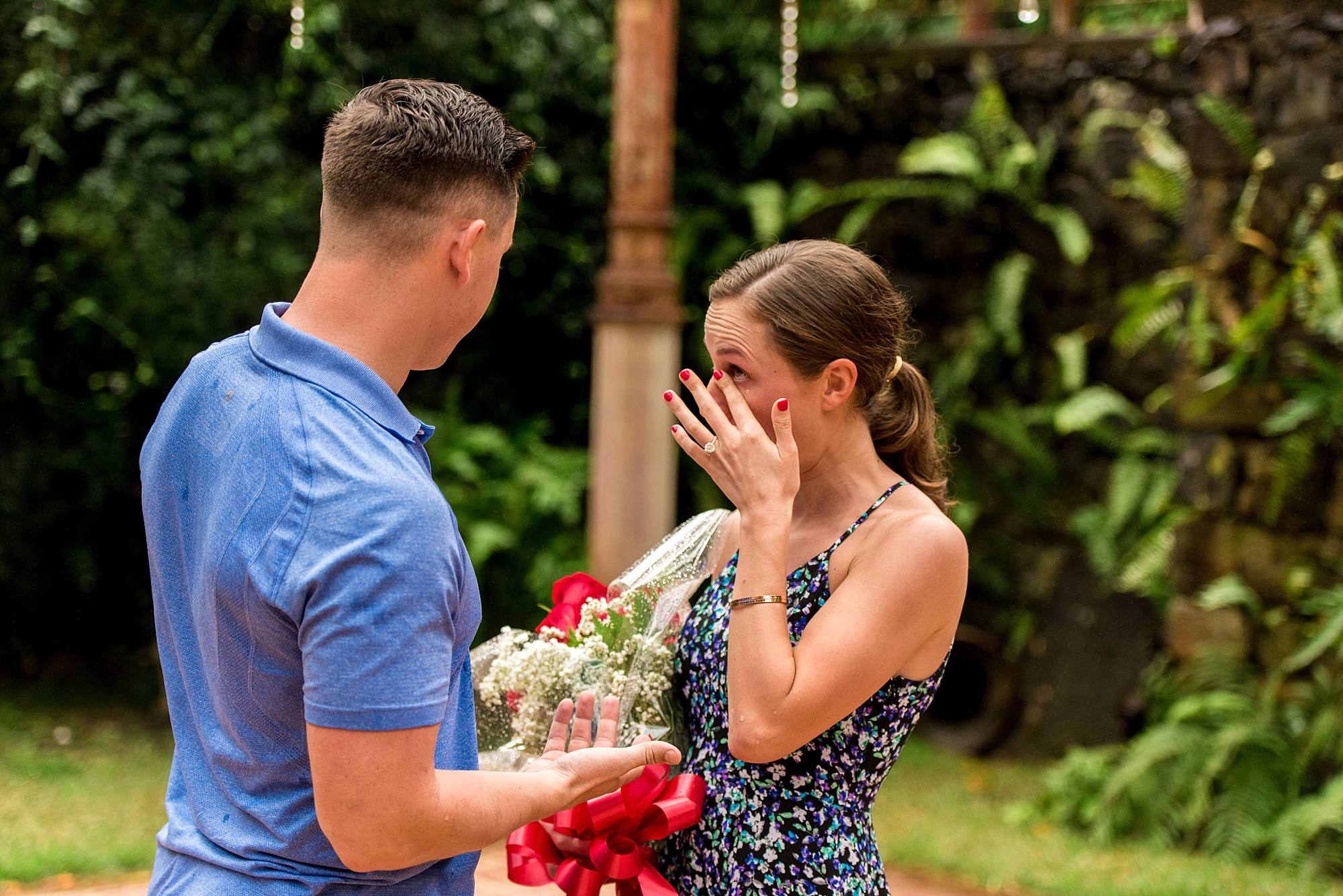 man giving woman flowers, woman wiping away tears after being proposed to