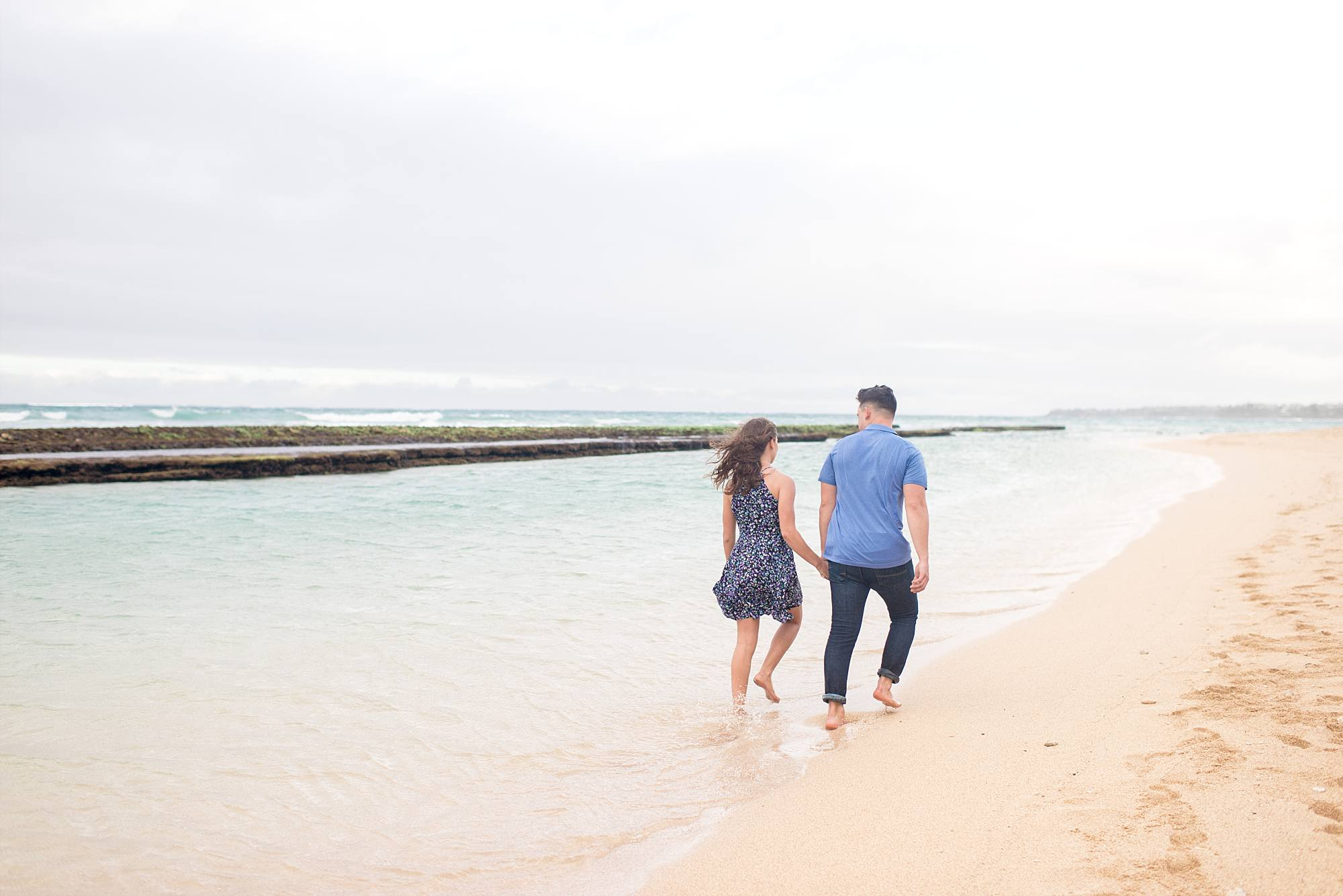 engaged couple walking down beach