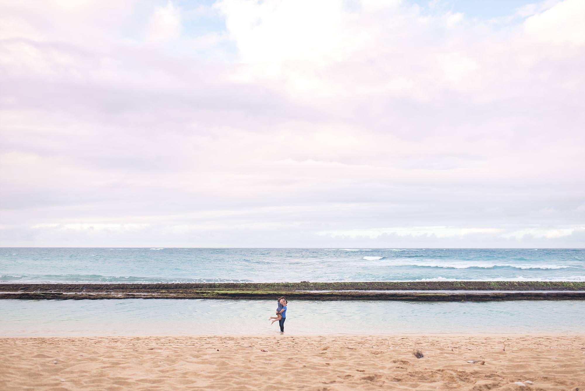 man swinging woman around at beach
