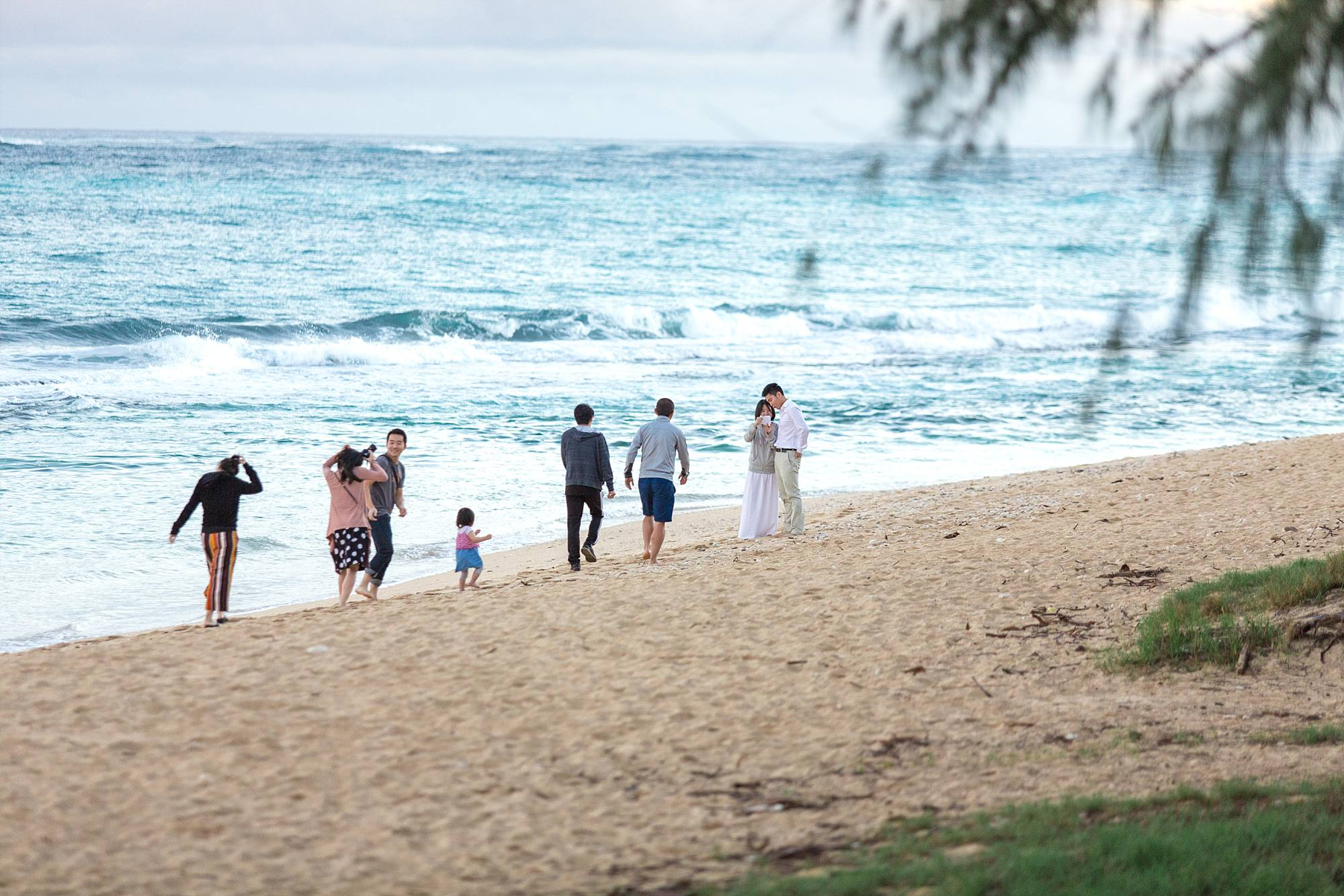 group of friends walking toward couple on the beach