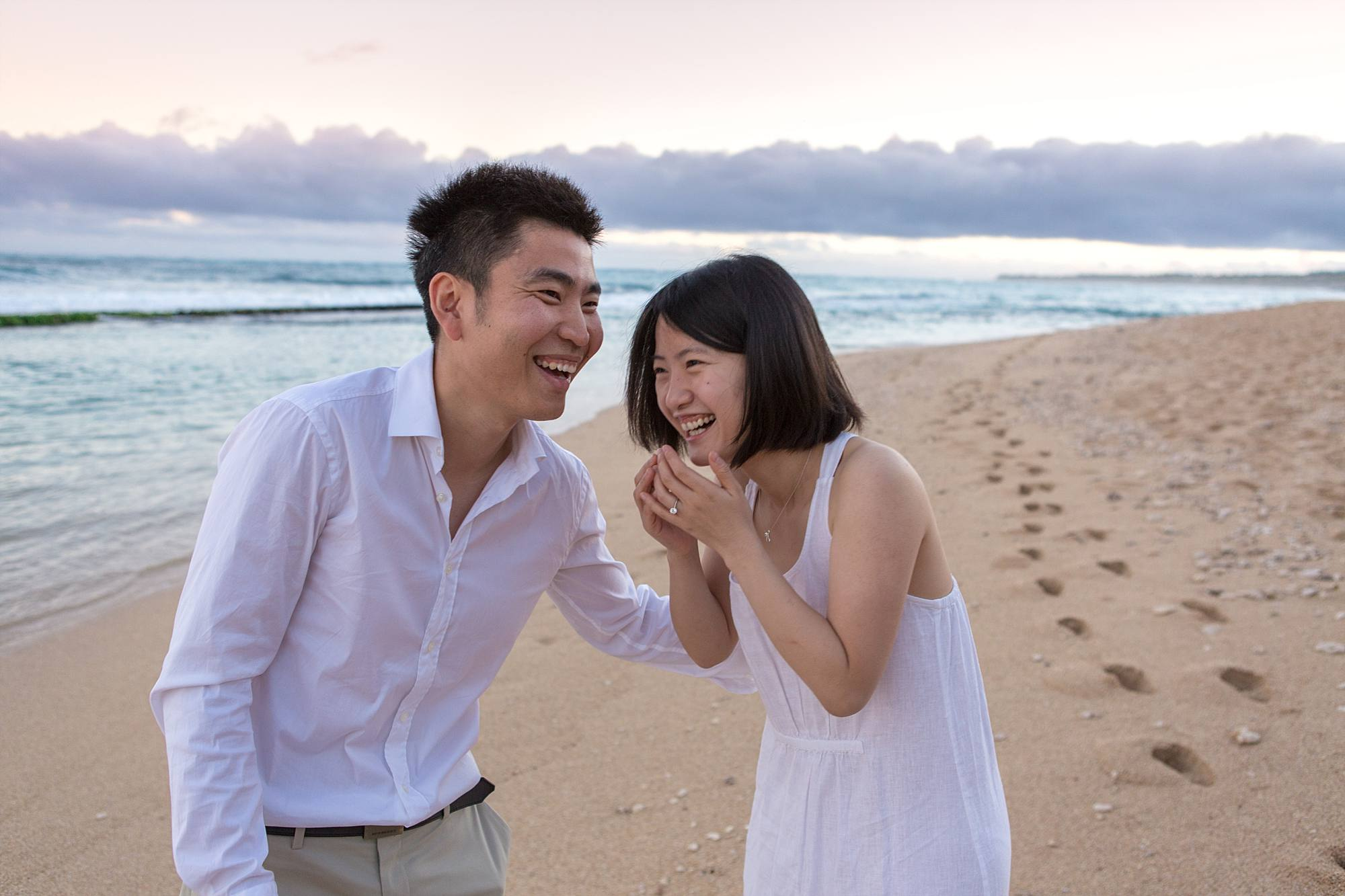 new fiances laughing on beach