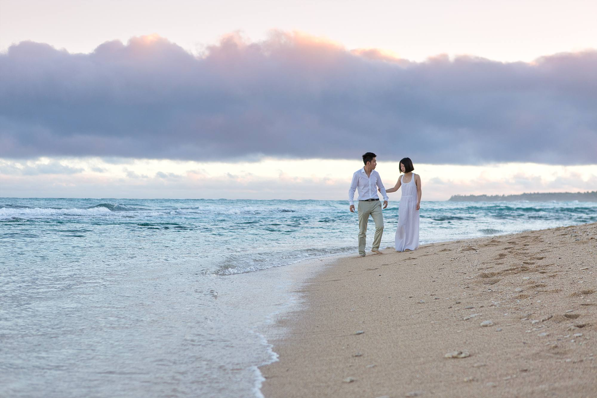 purple skies and couple holding hands in the gentle waves