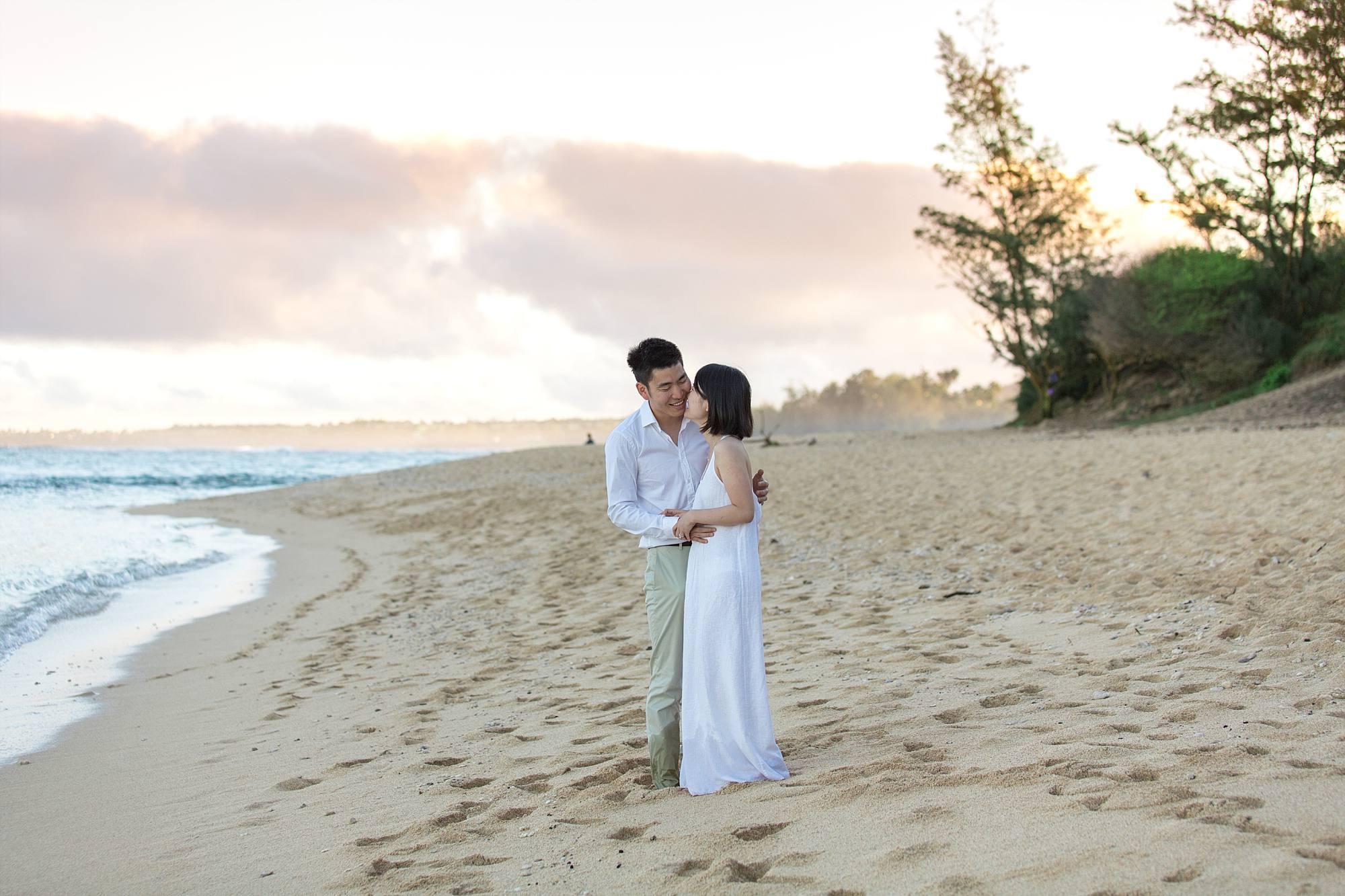 couple overlooking ocean, cuddling on beach