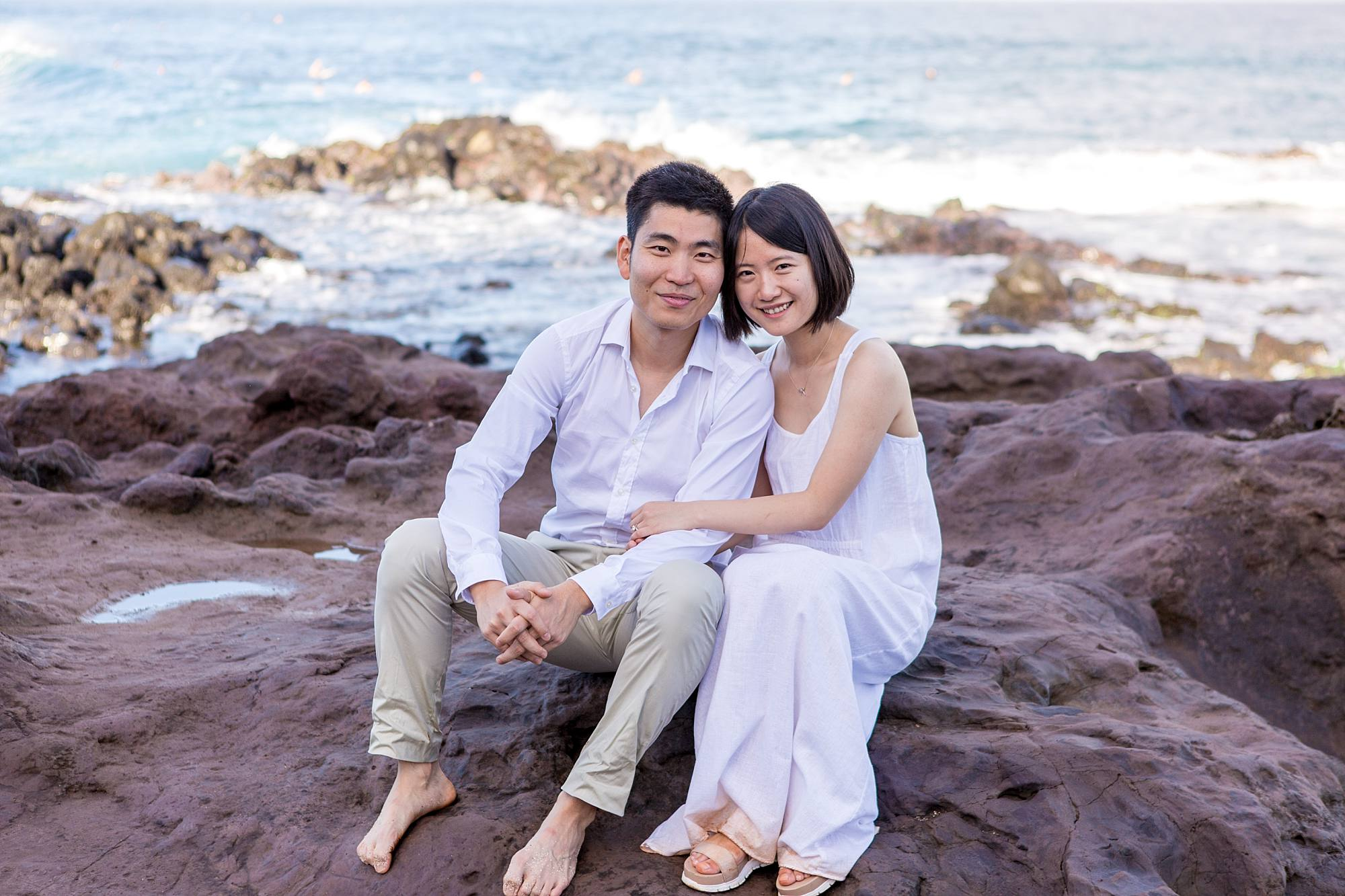 couple snuggling on the rocks with sea in the background