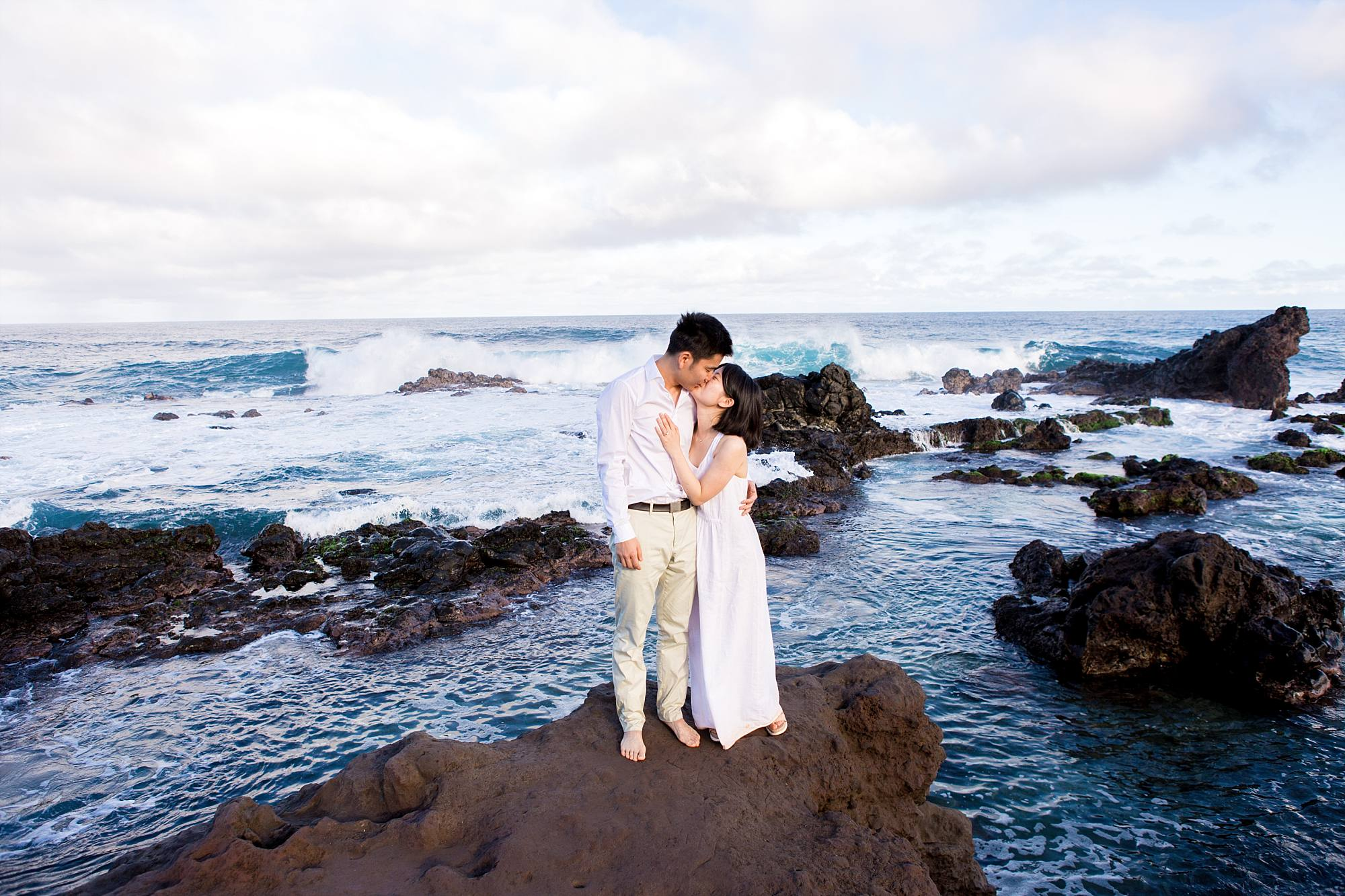 couple kissing on the rocks surrounded by the ocean
