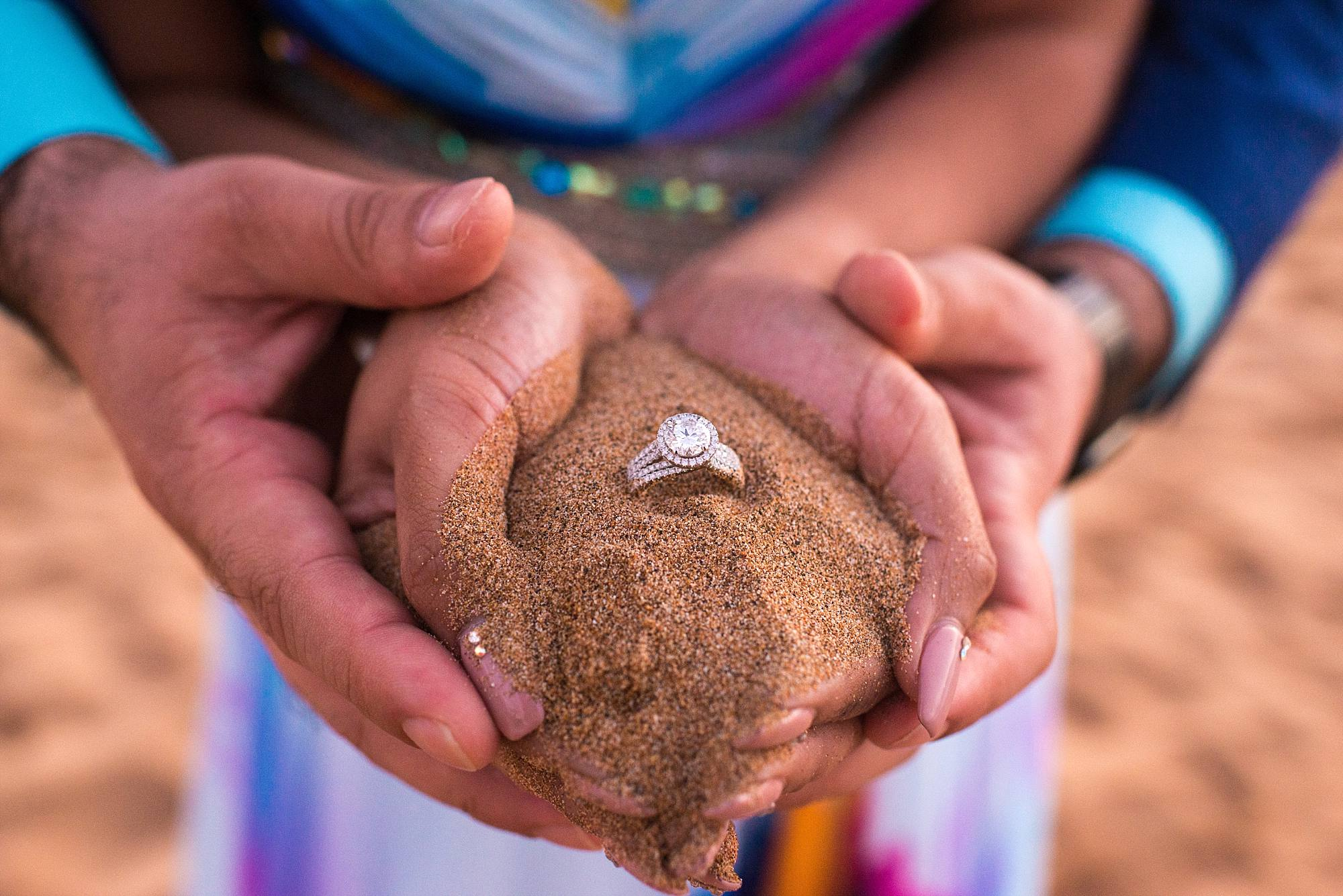 engagement ring in the sand within two hands