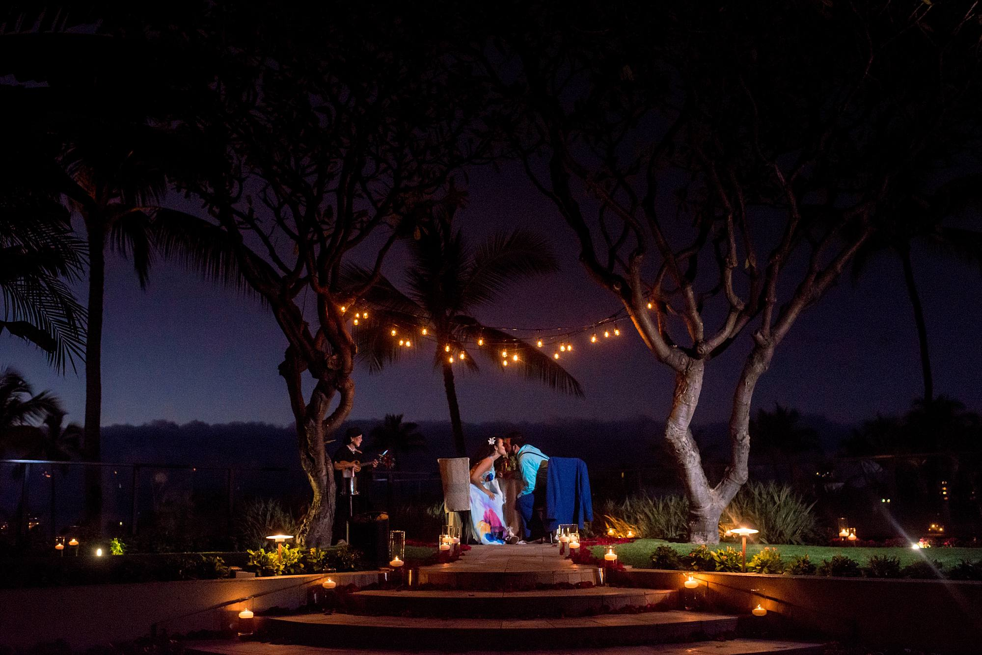 couple kissing at romantic dinner outdoors under the light