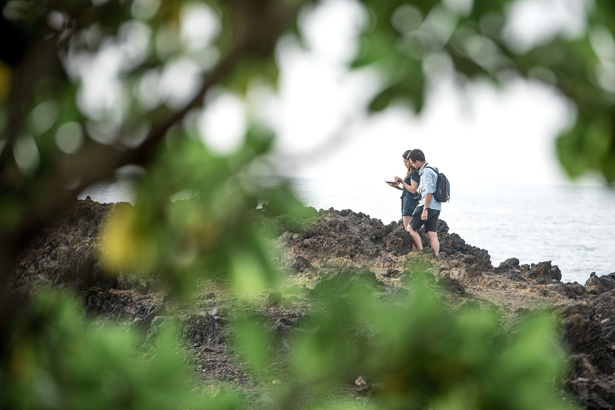 couple reading scavenger hunt clues on lava rocks on Maui