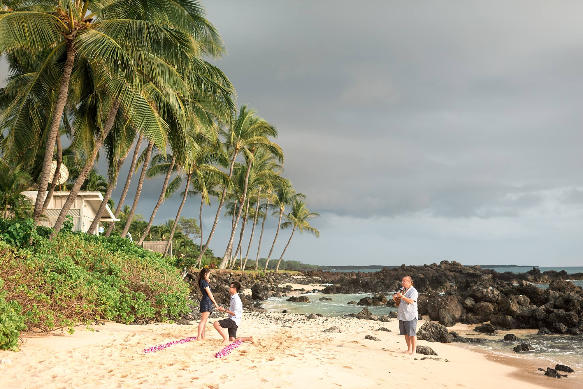 man down on one knee proposing on tropical Maui beach