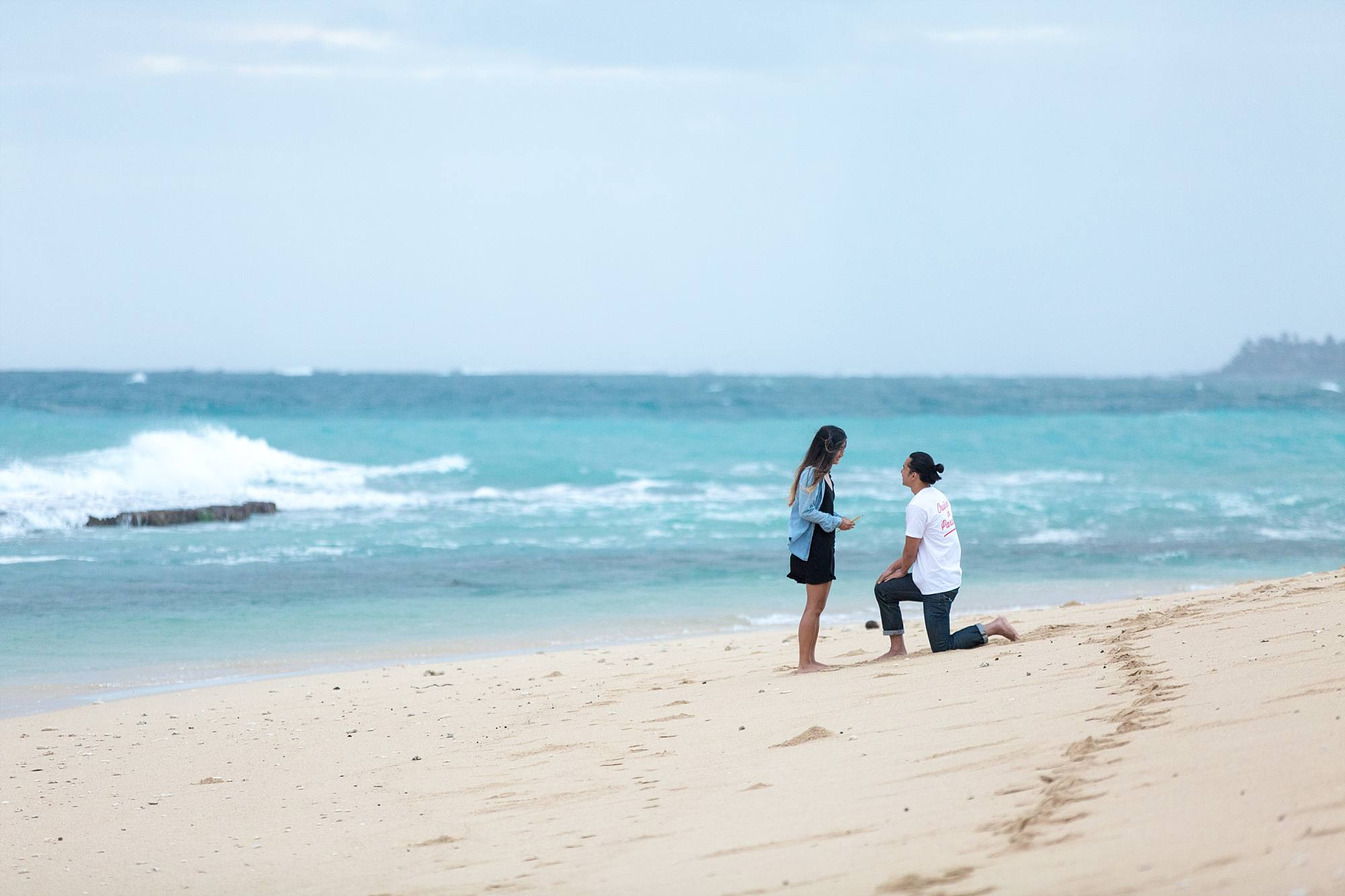 man down on one knee proposing on Maui's north shore