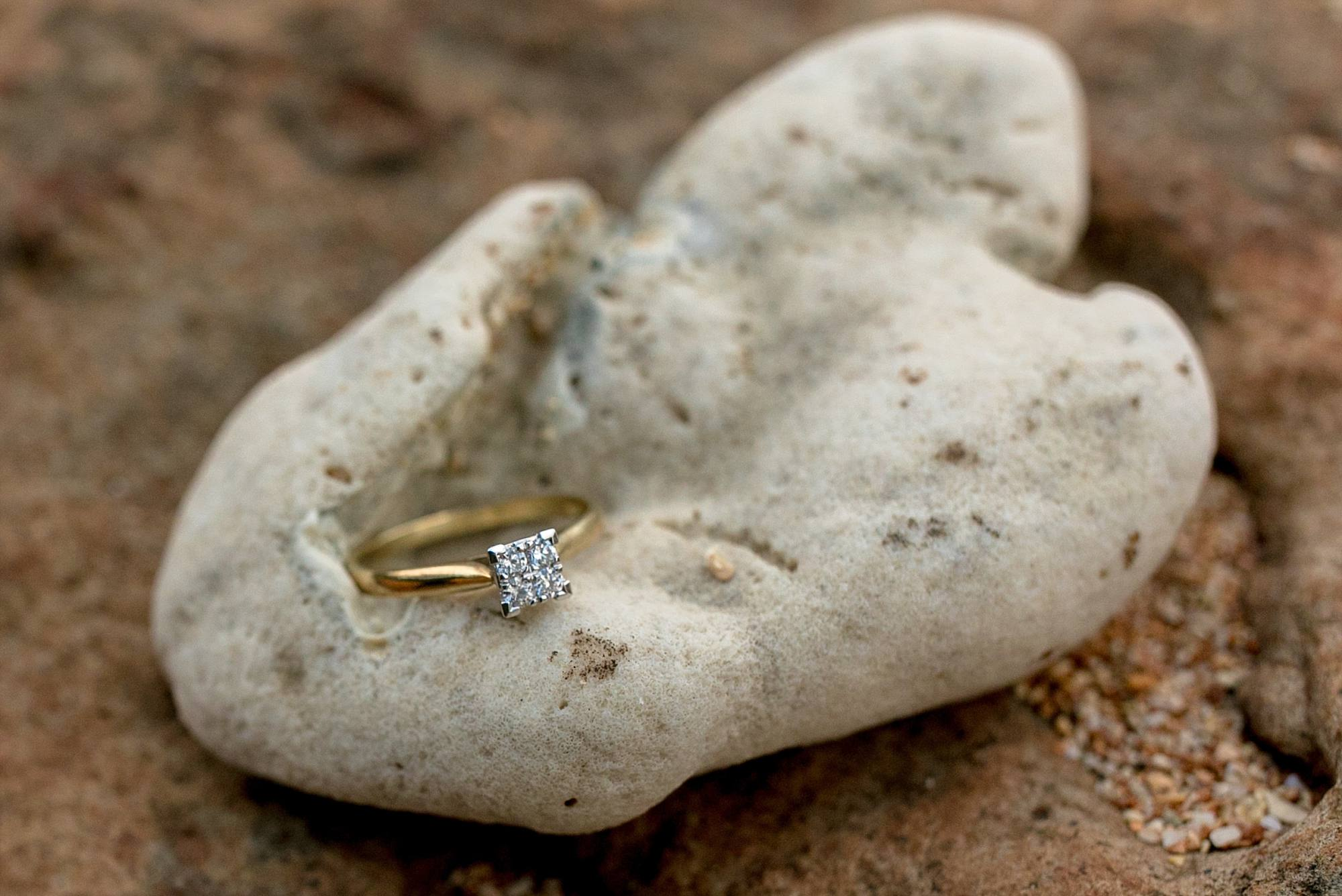 princess cut diamond engagement ring with gold band sitting atop beach rock