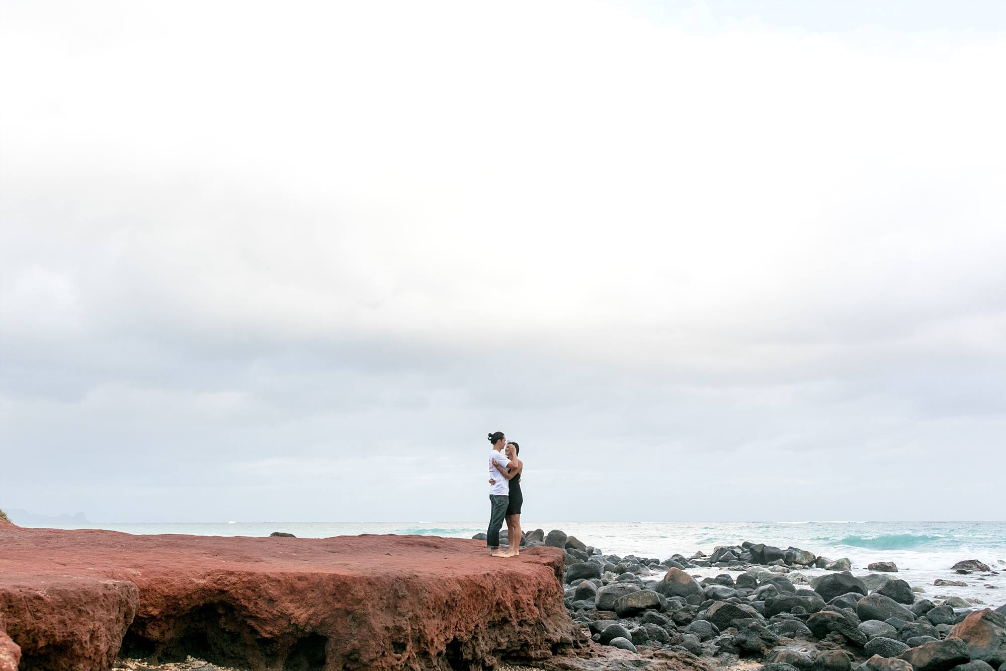 couple standing and hugging on red rock cliff Maui