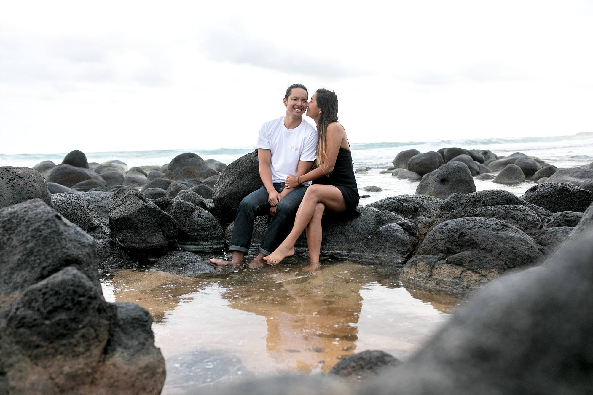 engaged couple sharing a snuggle sitting on rocks surrounding a tide pool