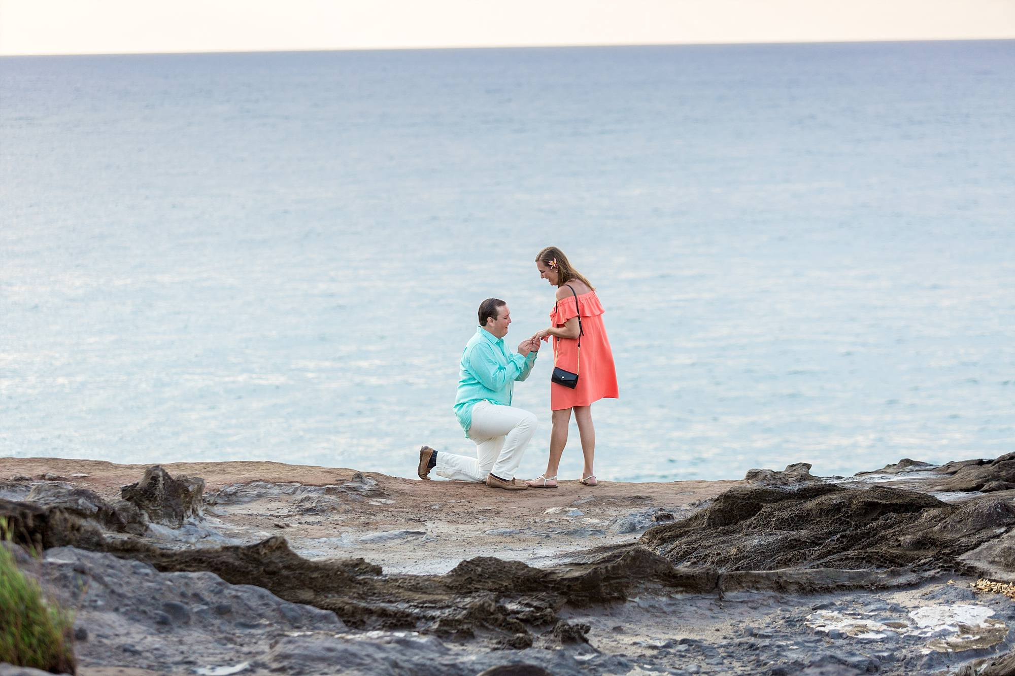 man down on one knee proposing on a Maui cliff