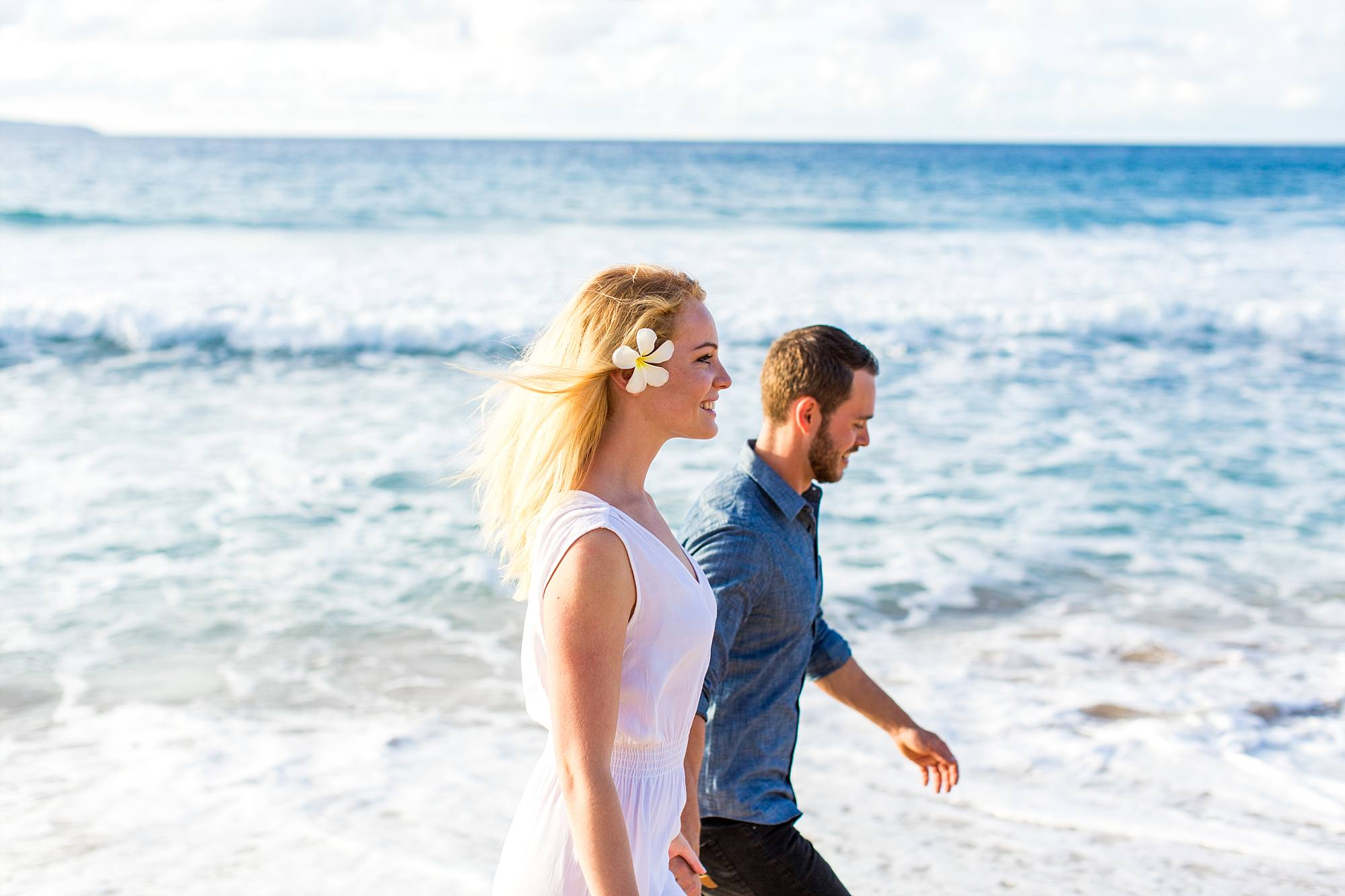 couple in love walking down beach together, side shot