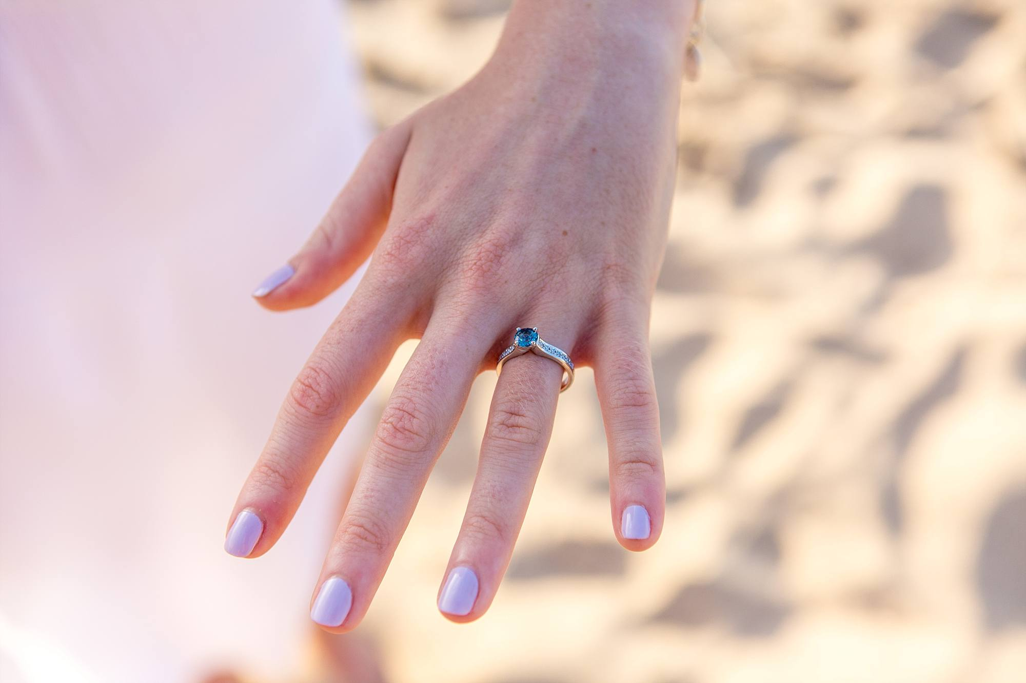 woman showing off her sapphire engagement ring