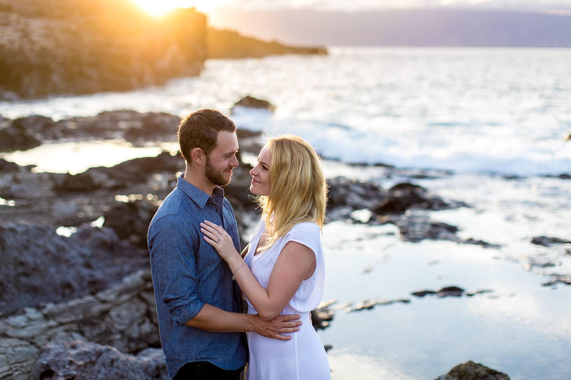 beautiful Maui sunset peeking over the rocks over newly engaged couple
