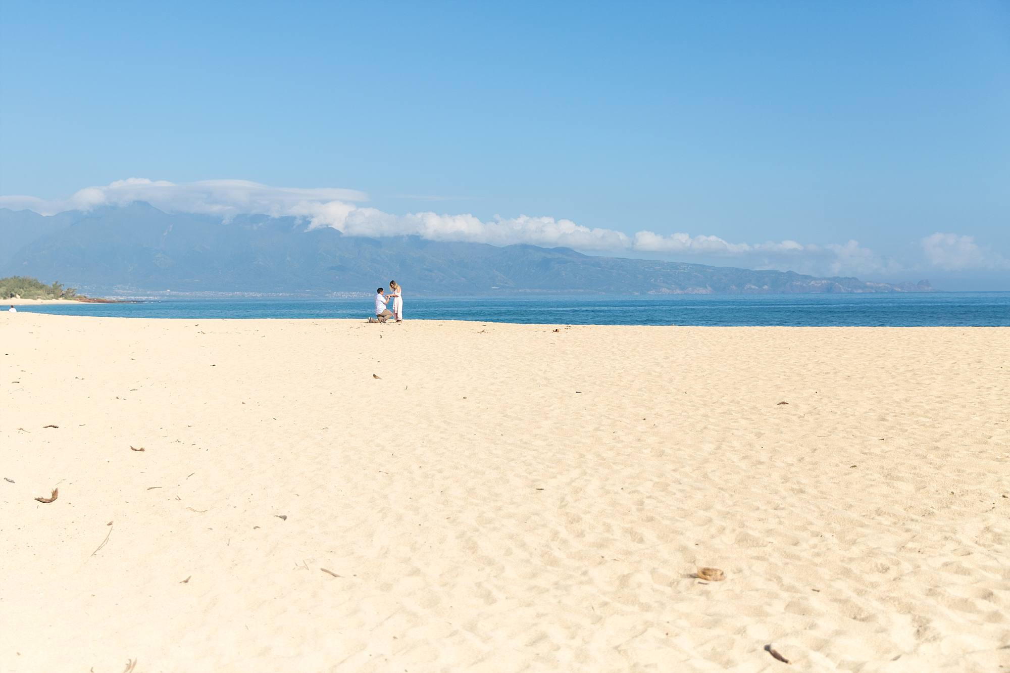 incredible shot of a man proposing to his girlfriend on beautiful white sand beach on Maui