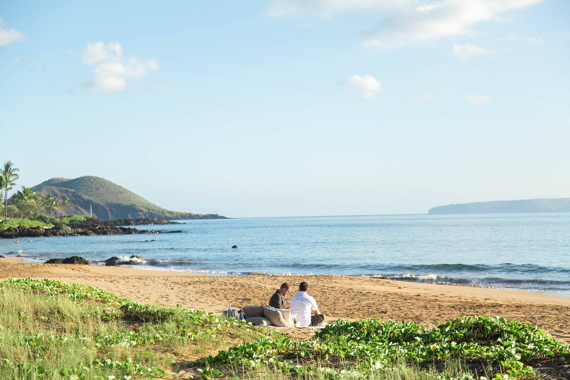 The men sitting down on their picnic blanket on the Maui beach, moments before a proposal!