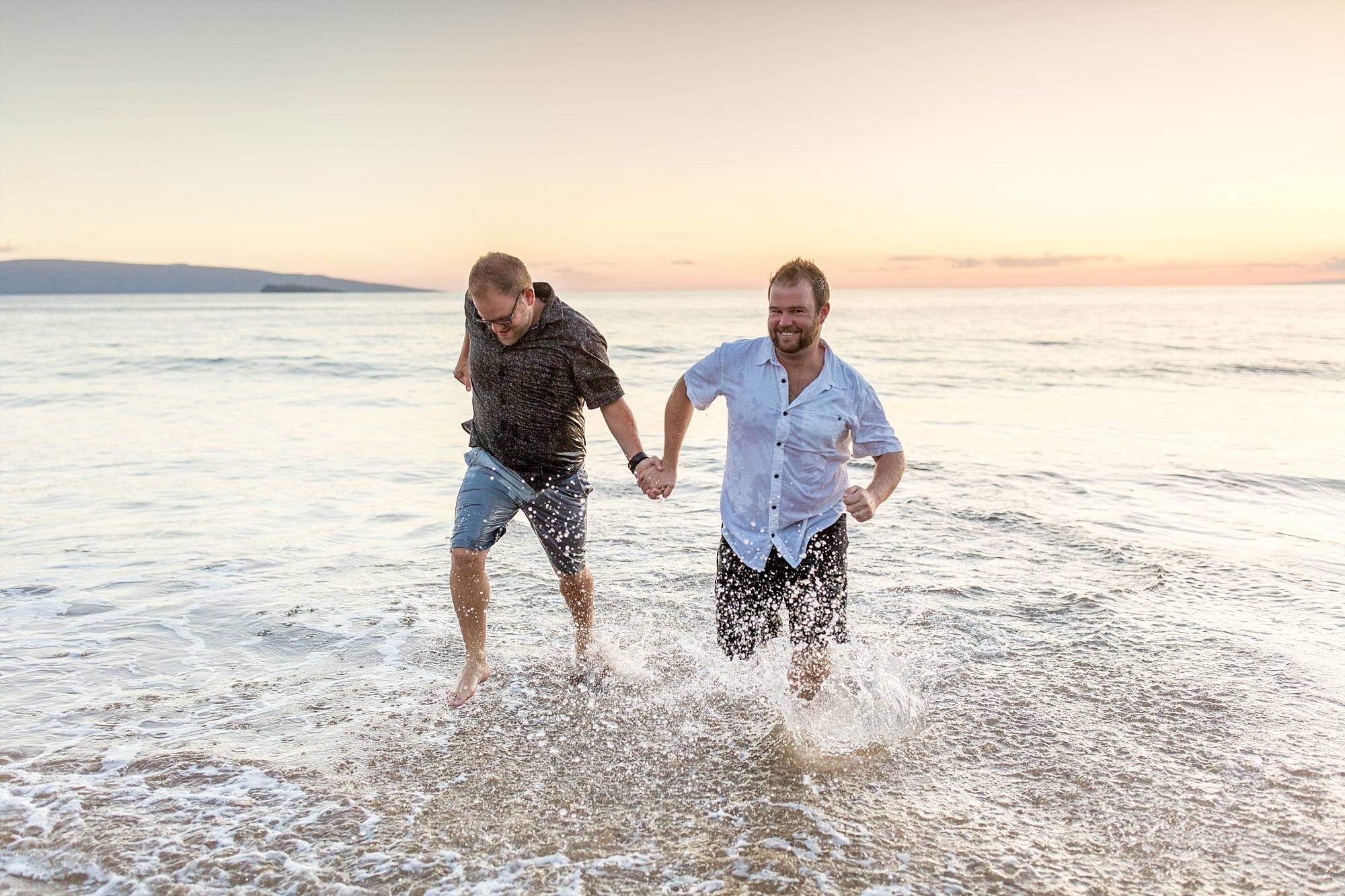 couple holding hands running through the water