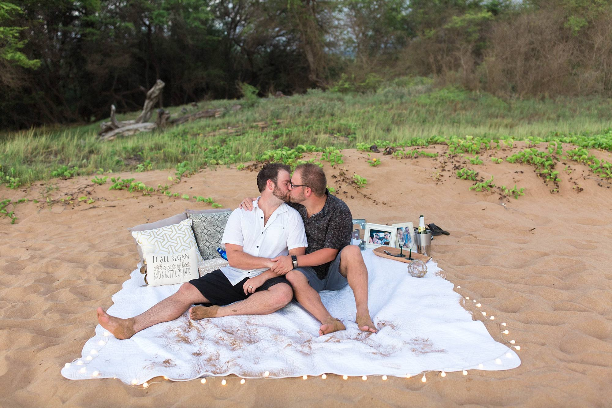 Newly engaged couple smooching on their romantic beach blanket