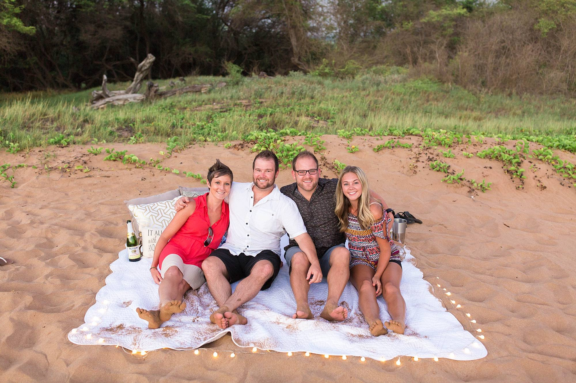 engaged couple and their friends all celebrating the engagement together in the sand