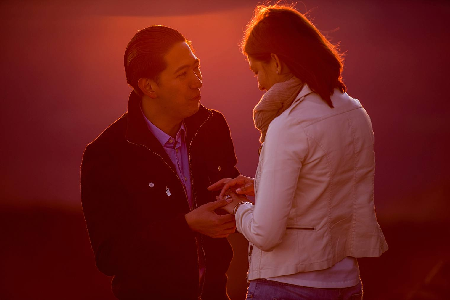 putting on engagement ring at sunrise