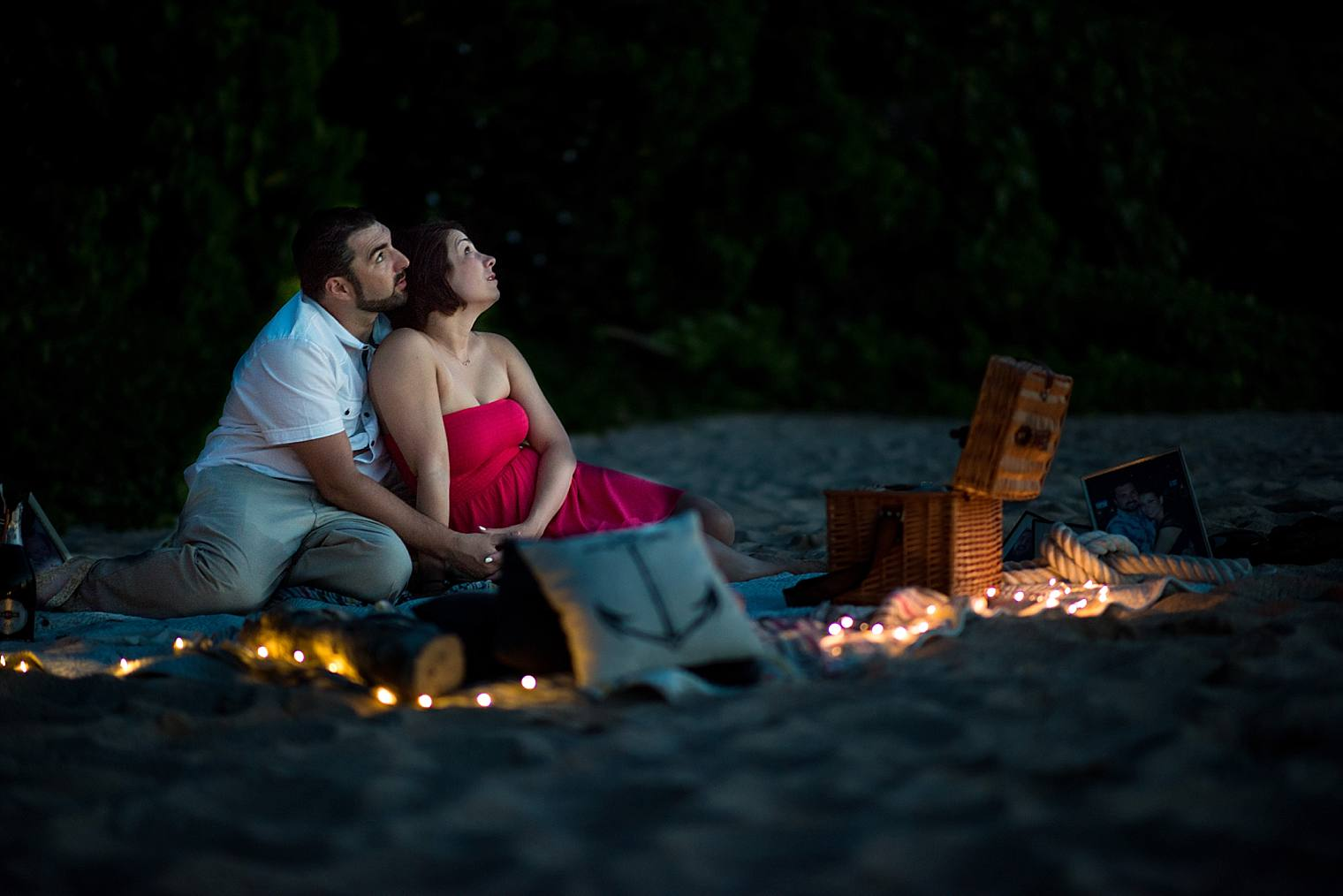 engaged couple looking up at stars on the beach