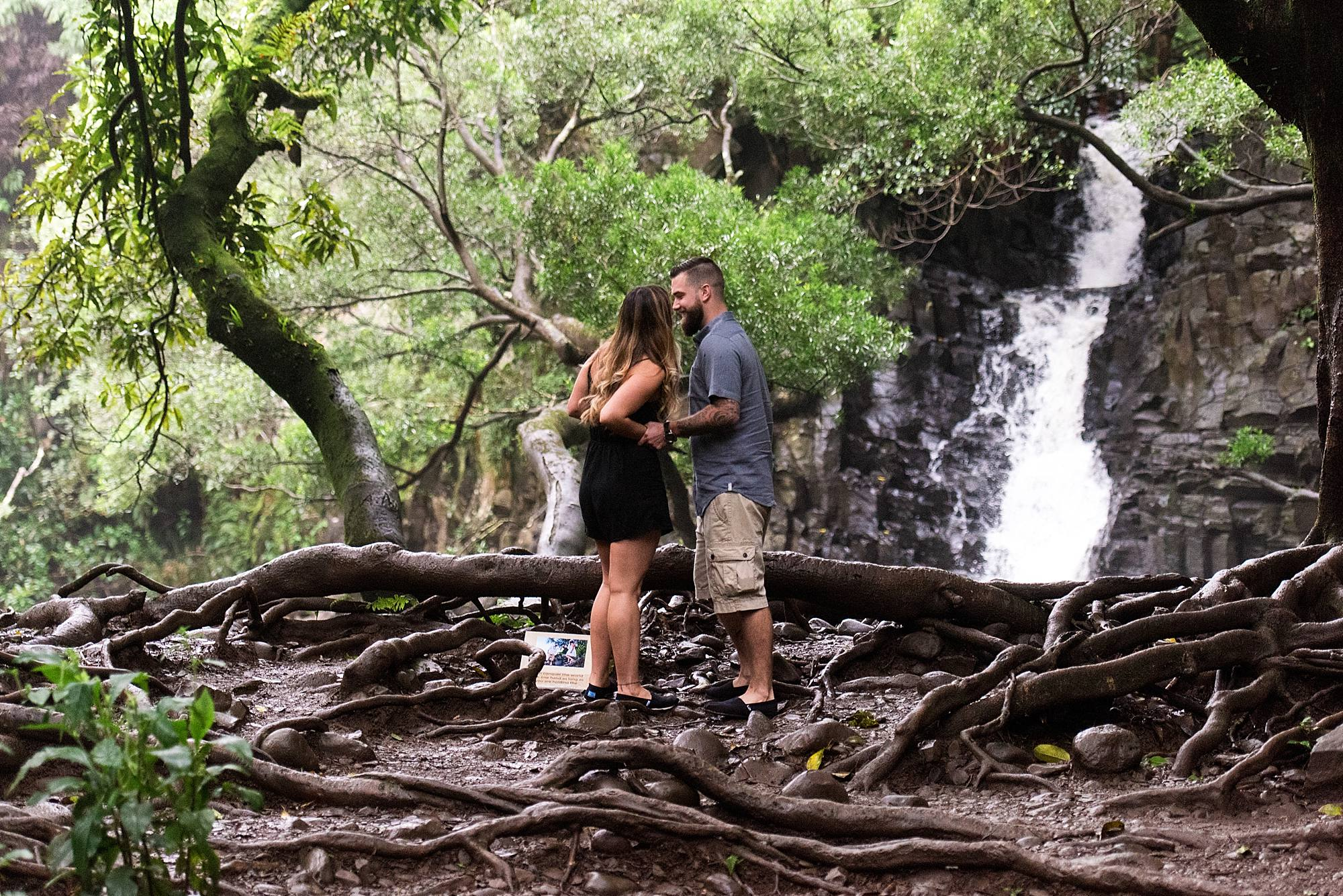 the moment before he proposes in front of waterfall