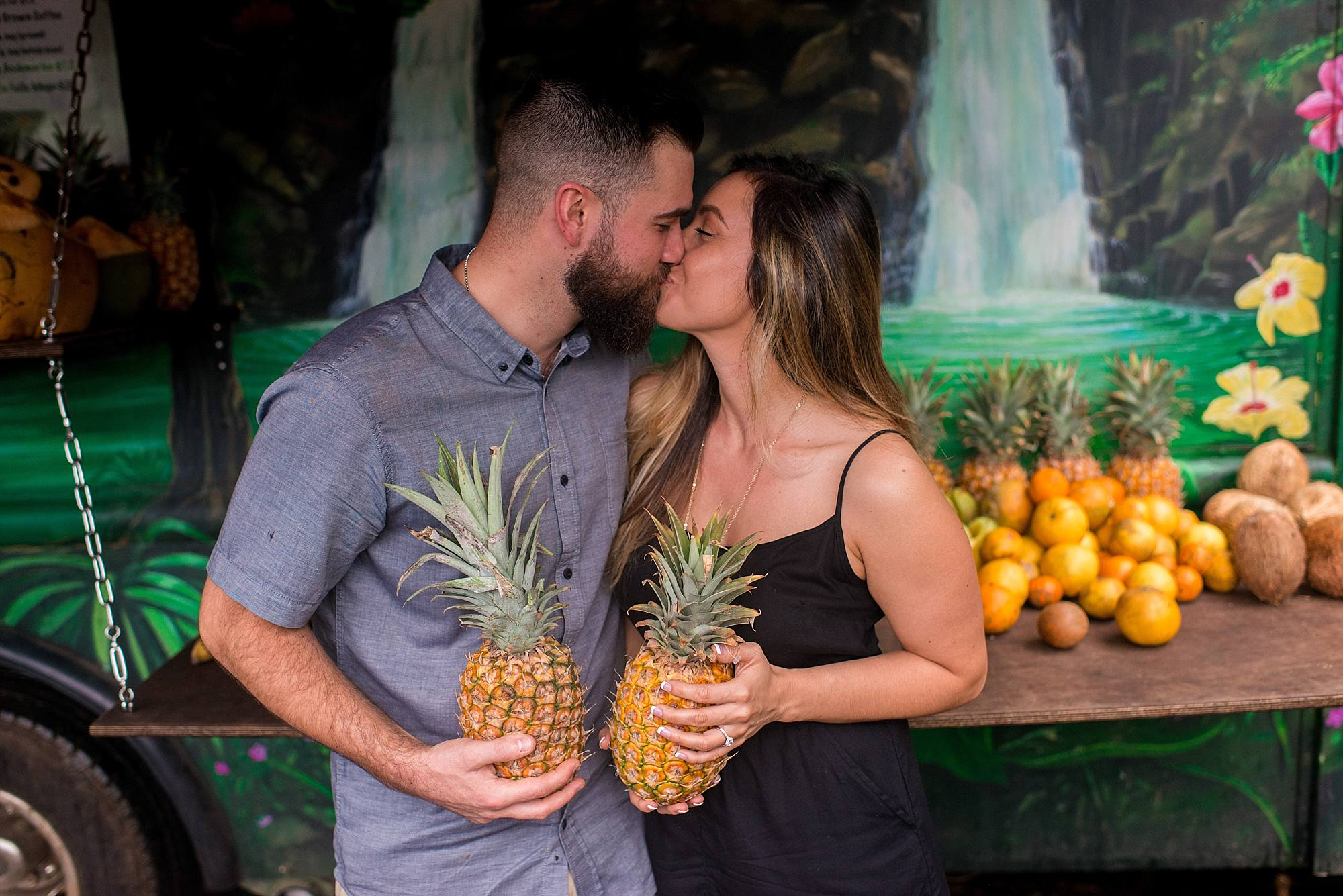 engaged couple holding pineapples