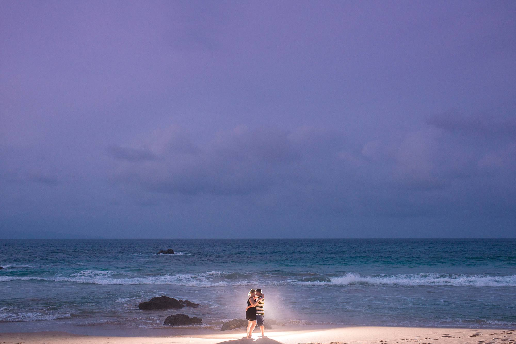 backlit couple kissing in front of the ocean