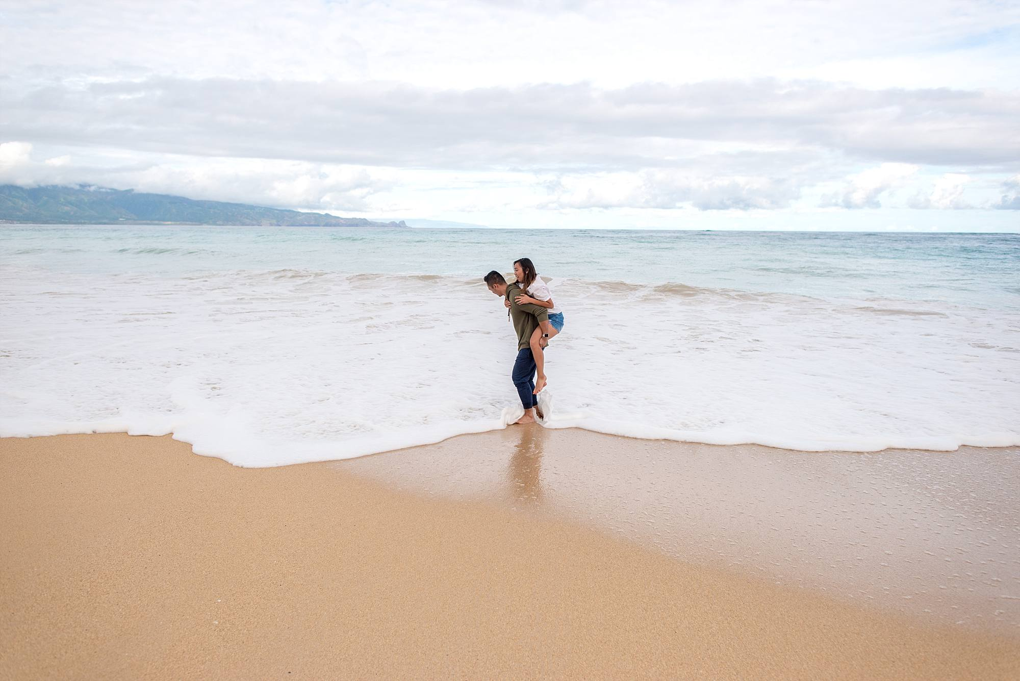 man carrying fiance on his back in the waves