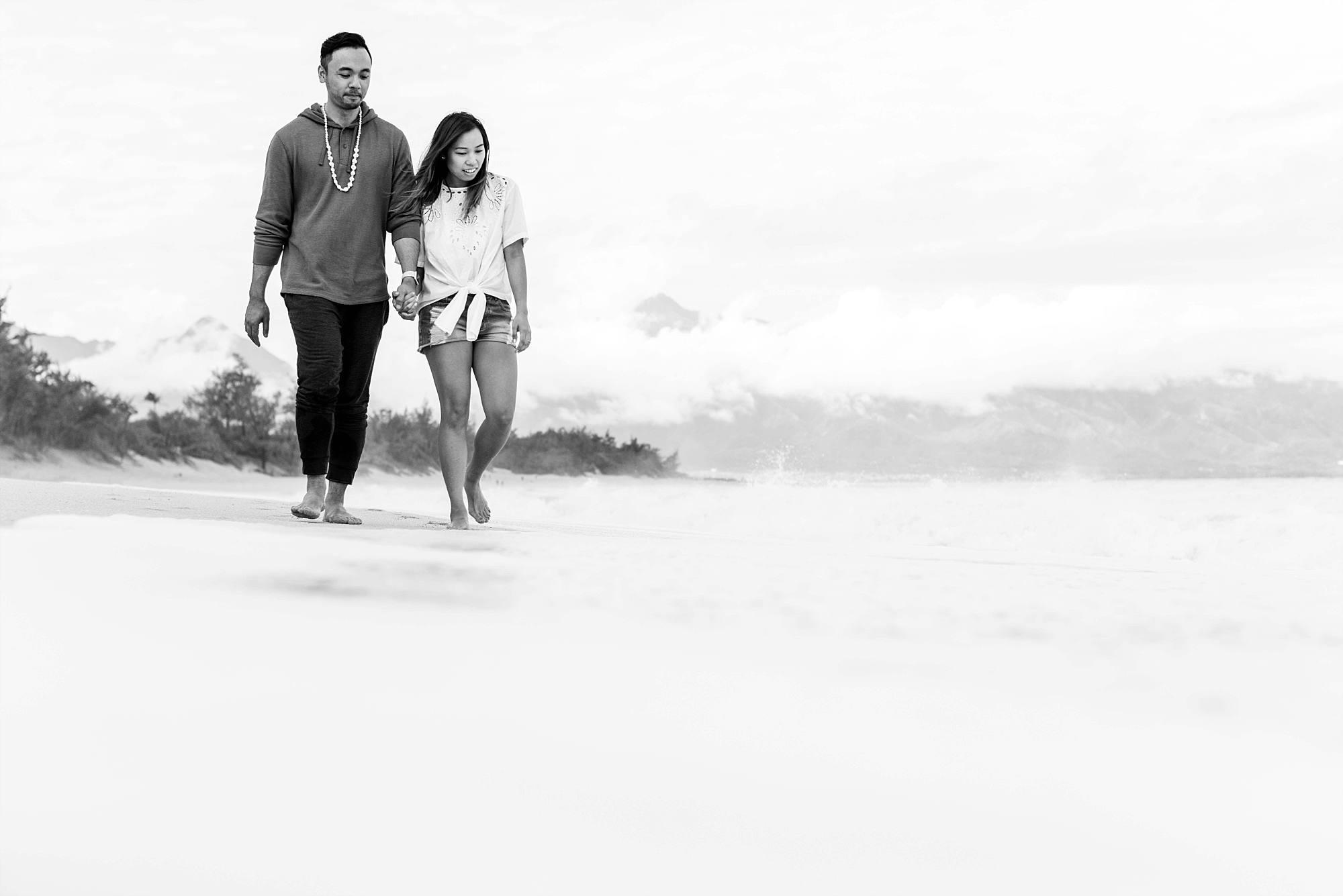 black and white photo couple walking on beach