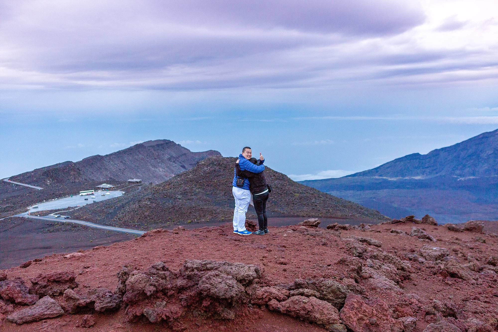 newly engaged couple hugging on top of mountain
