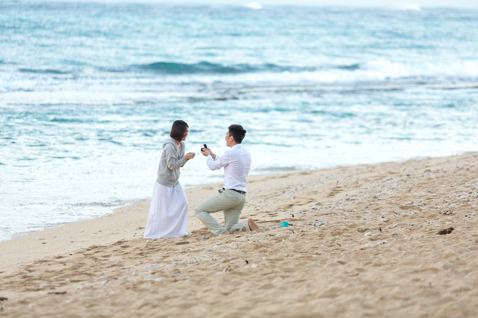 man asking woman to marry him on beach