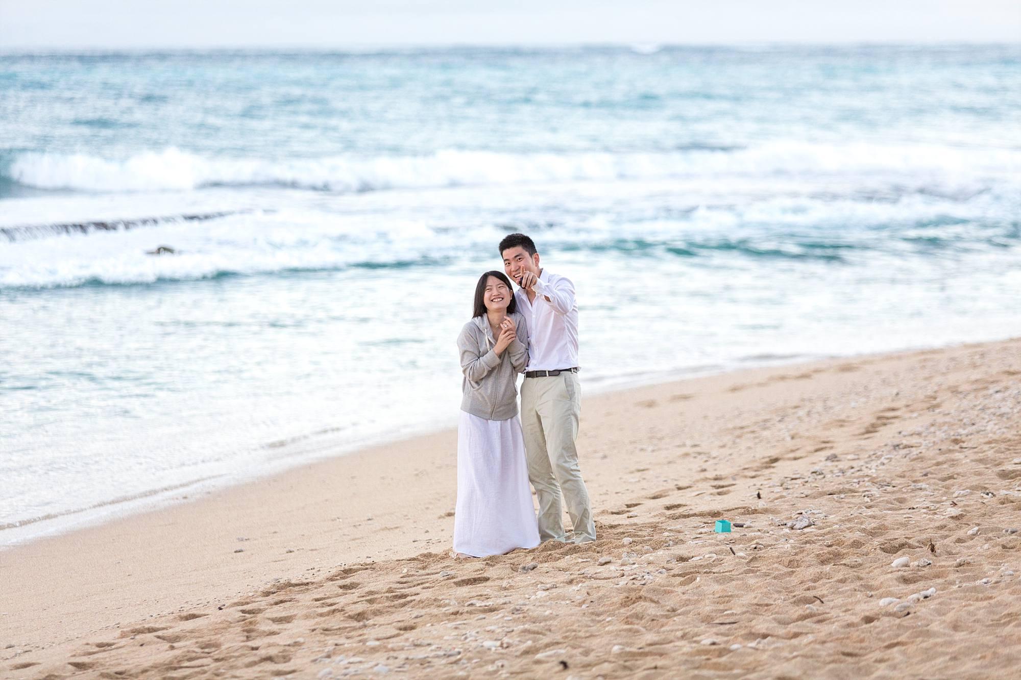 surprised new fiances on beach